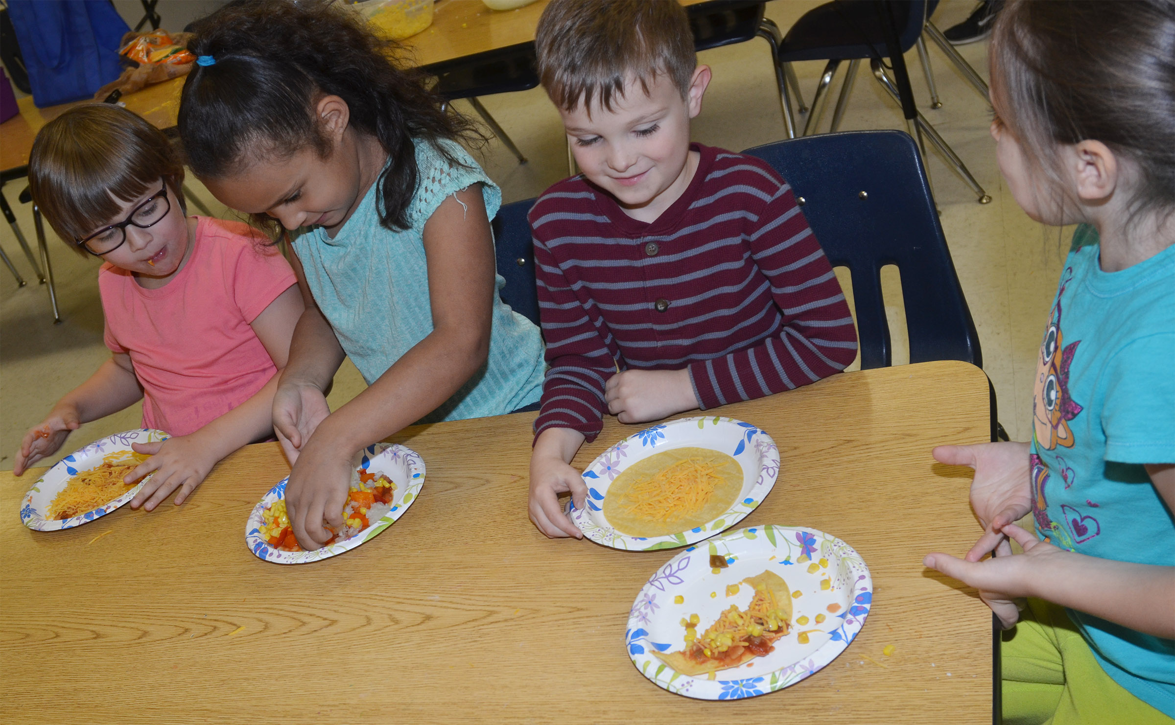 From left, CES first-graders Addelyn Dooley, Amani Bridgewater, Karson Burchett and Serenity Taylor enjoy their Mexican pizzas.
