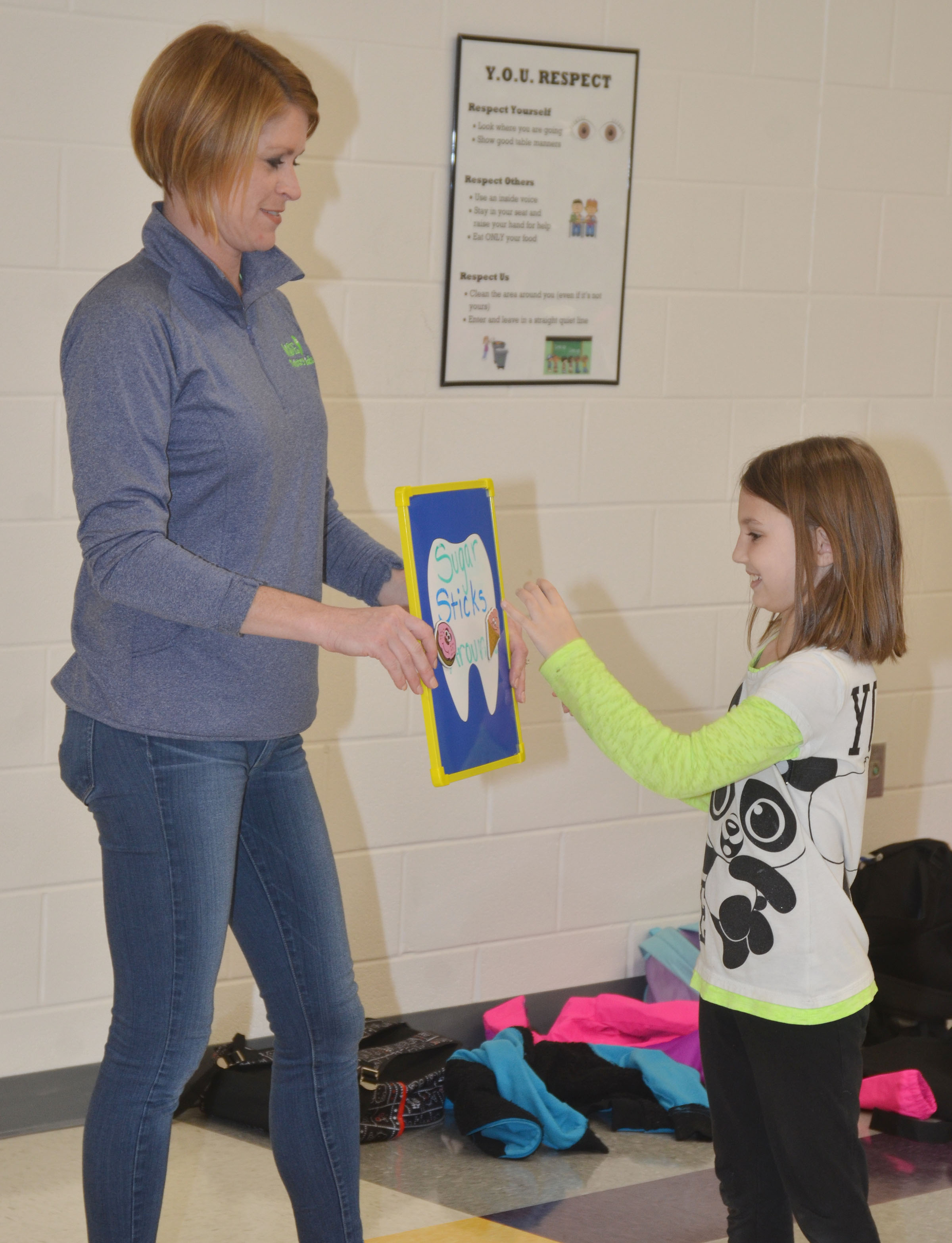 Dr. Heather Wise of Wise Dentistry for Kids asks CES second-grader Kairi Tucker if ice cream is a good snack.
