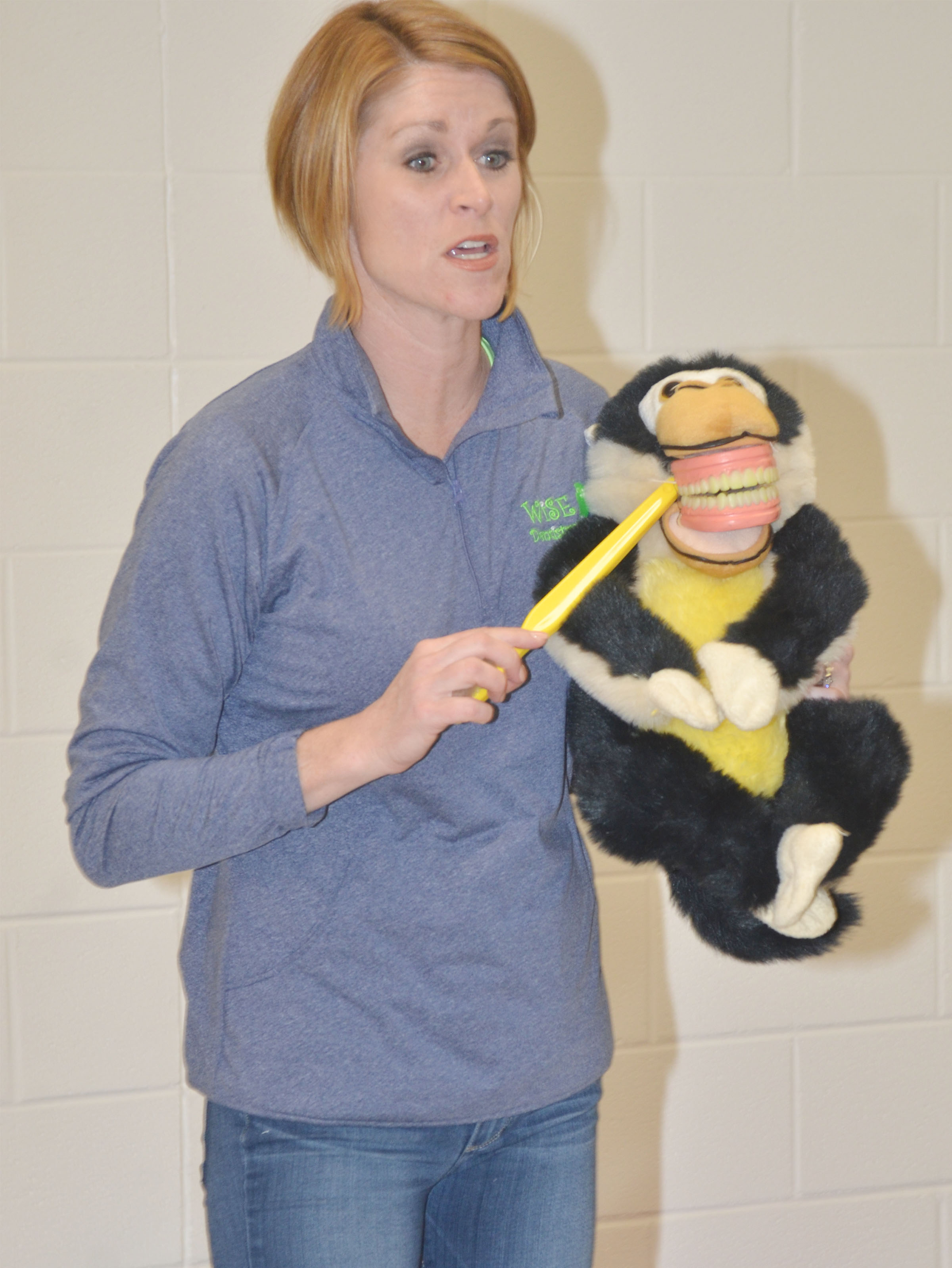 Dr. Heather Wise of Wise Dentistry for Kids demonstrates for CES Wings Express students the proper way to brush their teeth.