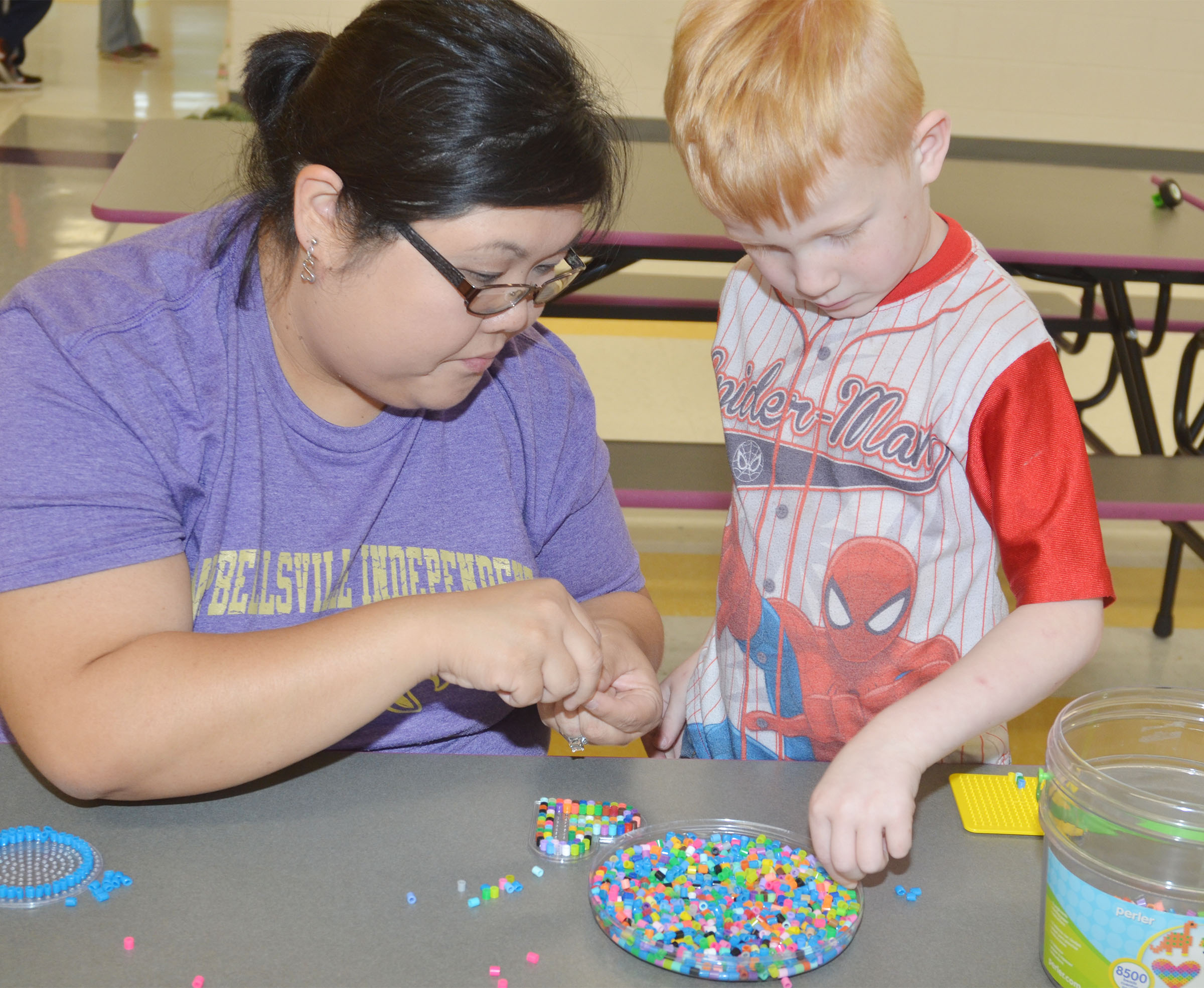 CES kindergartener Jayden Maupin uses beads to make a heart with kindergarten assistant Brittany Johnson.