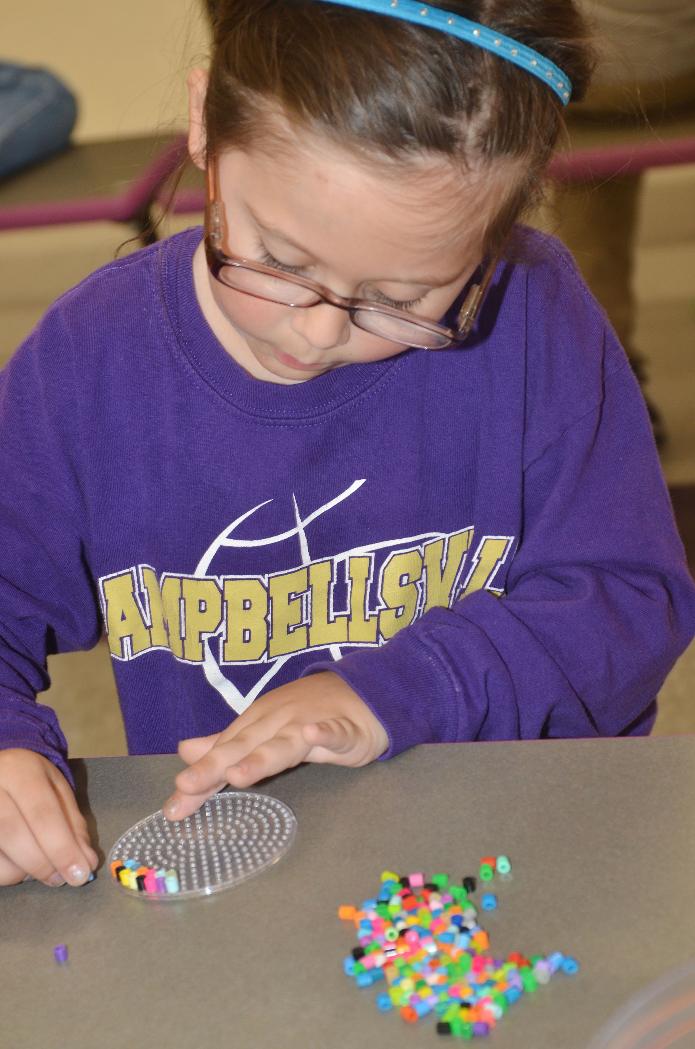 CES kindergartener Trinity Clark makes a circle out of beads.