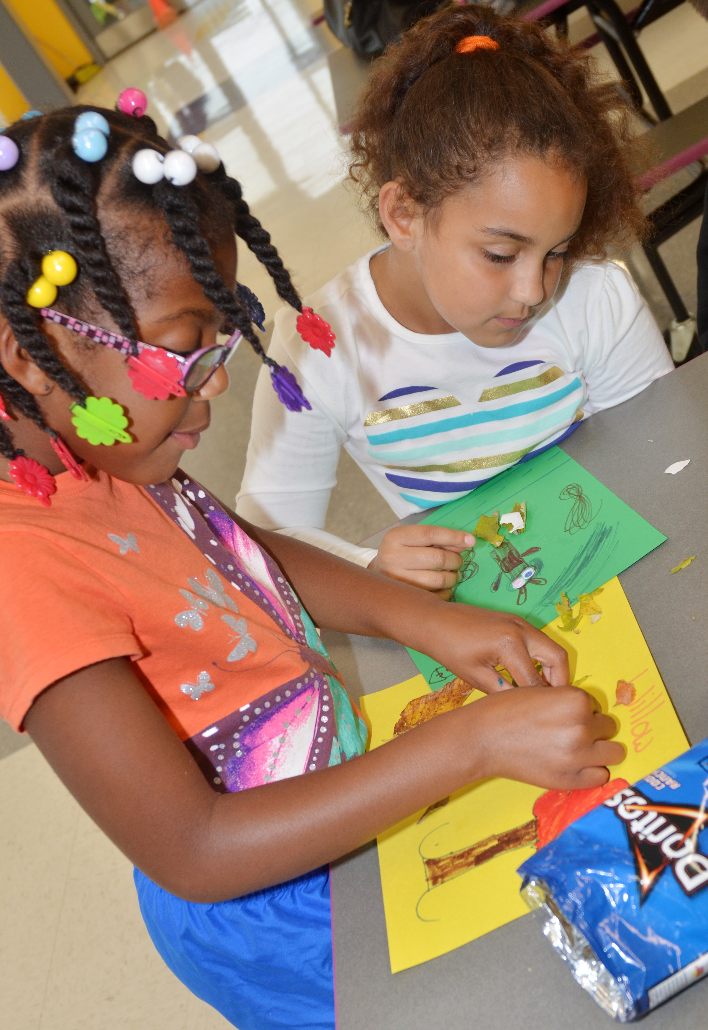 CES second-graders Willow Griffin, at left, and Maleigha Travis make animals out of leaves.