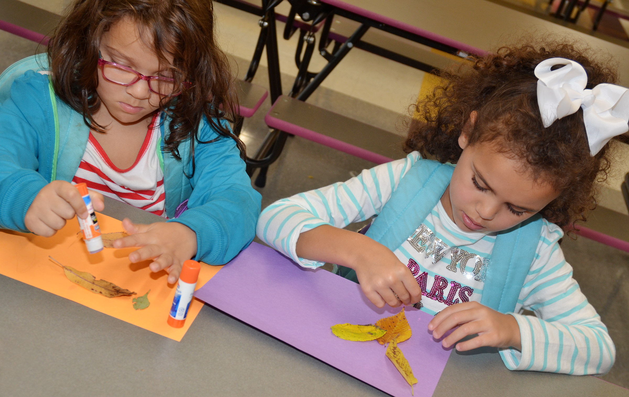 CES kindergarteners Addisyn Taylor, at left, and Adelyn Litsey use leaves to make animals.