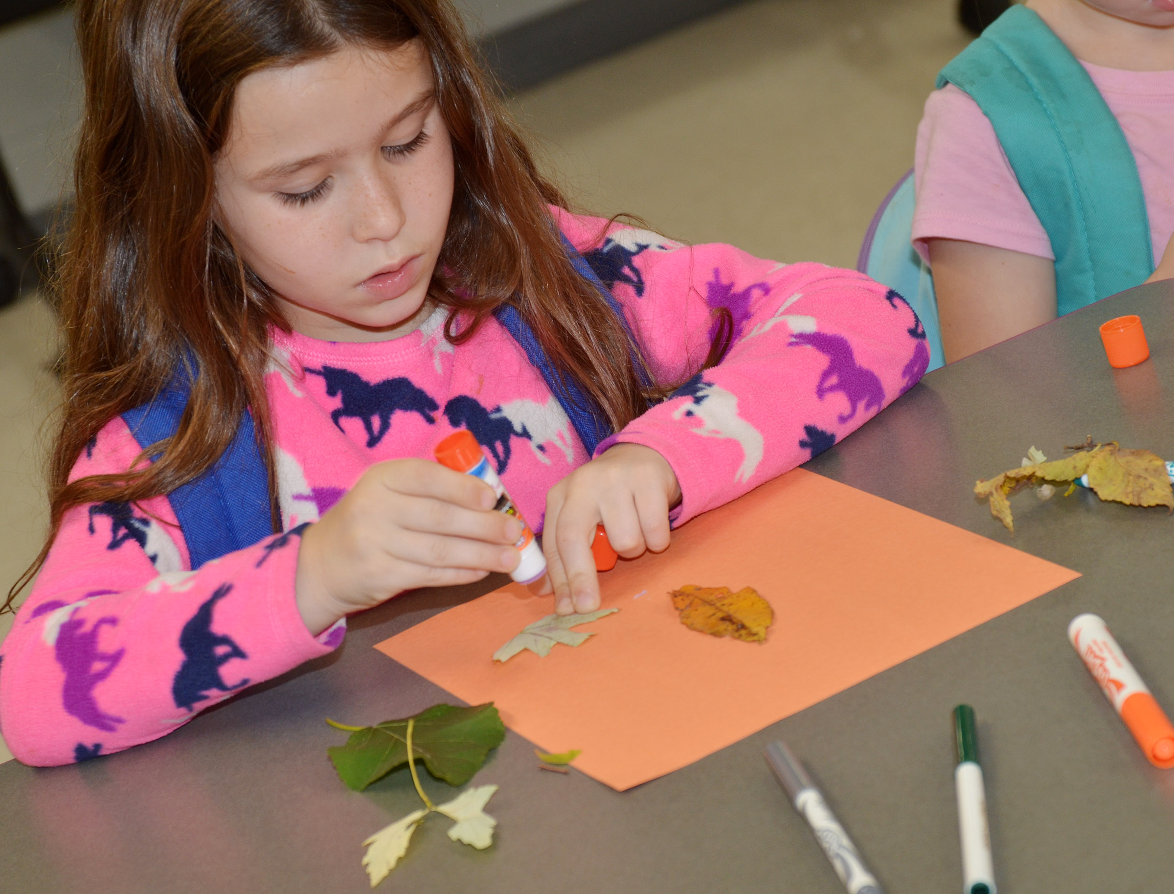 CES first-grader Stella Newcomb uses leaves to make an animal.