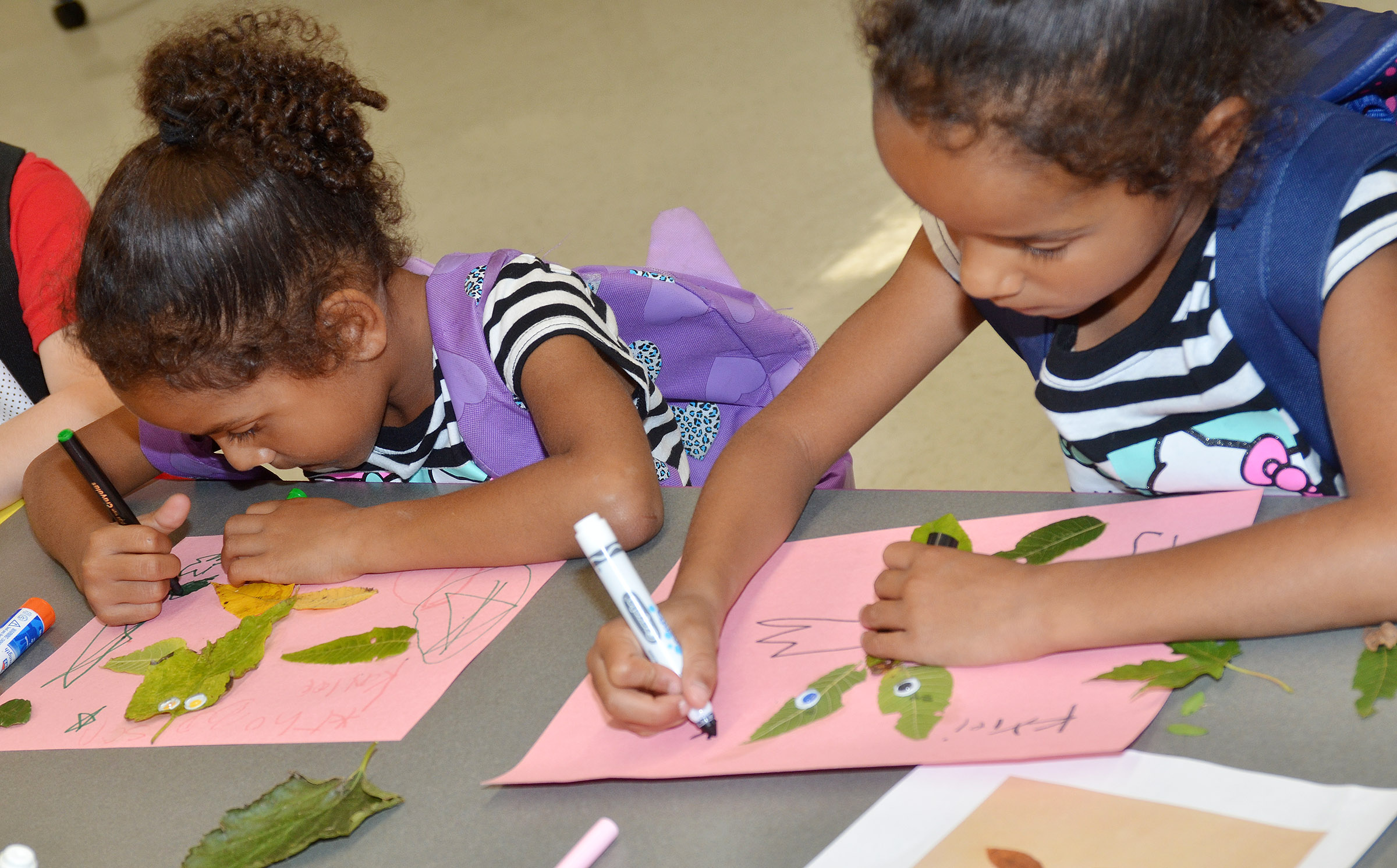 CES first-graders Kaylee Thompson, at left, and Kylei Thompson draw on their leaf animals.