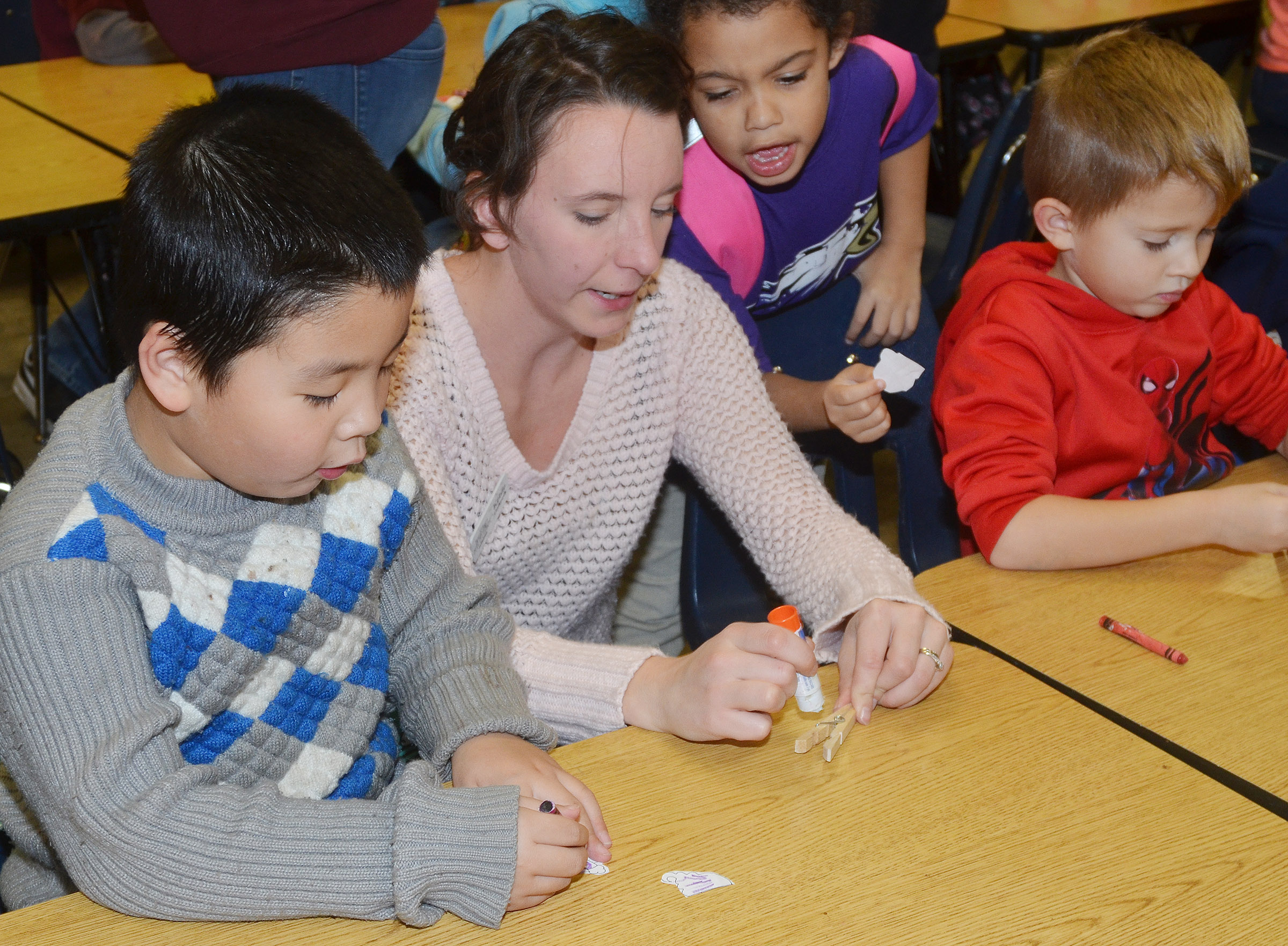 Kelsie Pepper from the Taylor County Public Library helps, from left, CES kindergarteners Victrin Ramsey, Rylee Karr and Andrew Stout make their Santa clothespins.