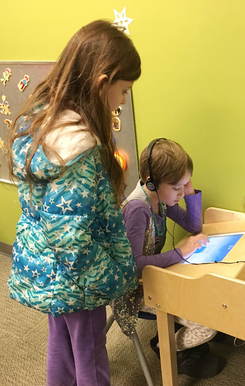 CES third-graders Madie Gebler, at left, watches as classmate Katie Nunn plays a game on a tablet.