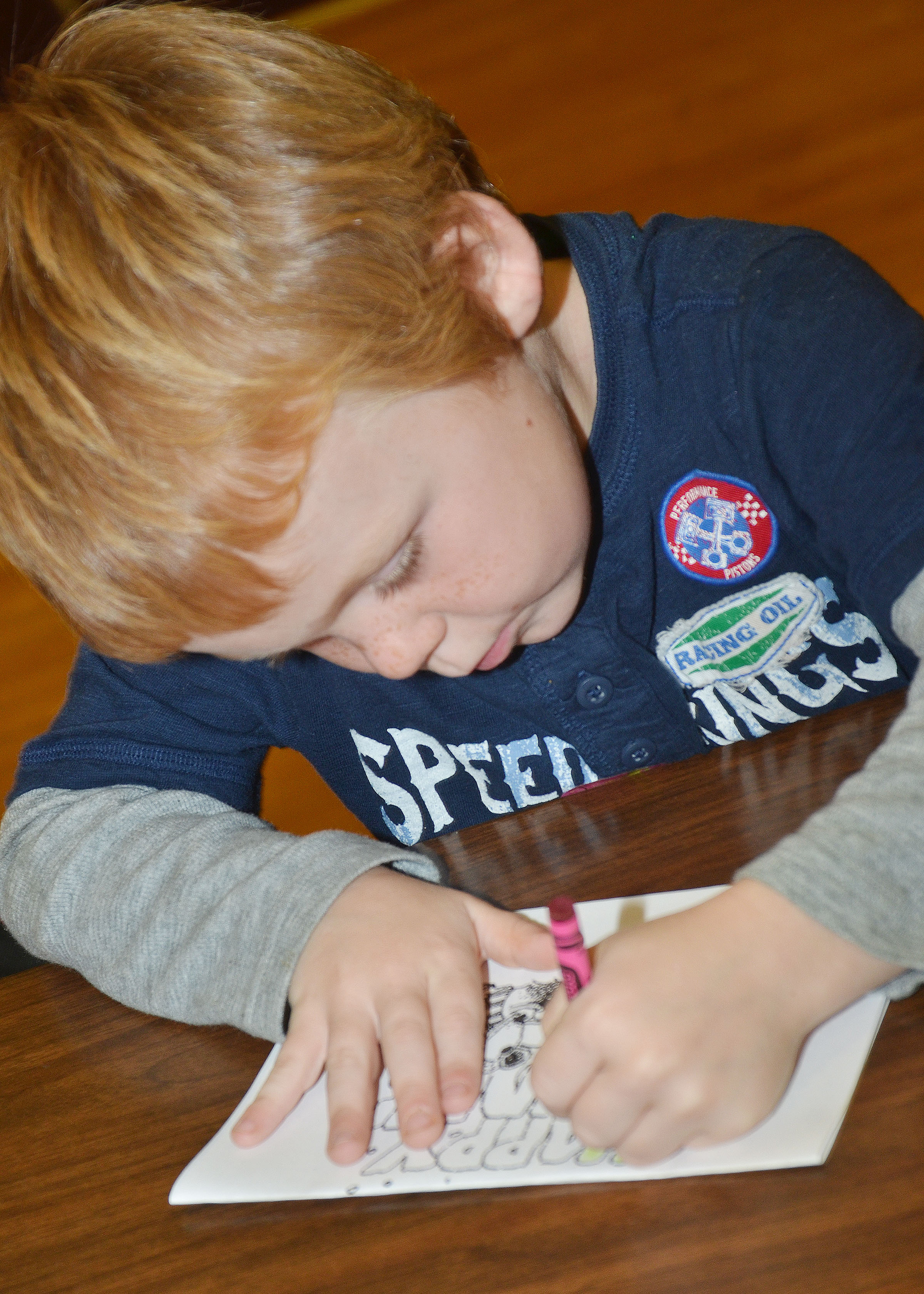 CES kindergartener Daven Davis colors a holiday card for a solider.