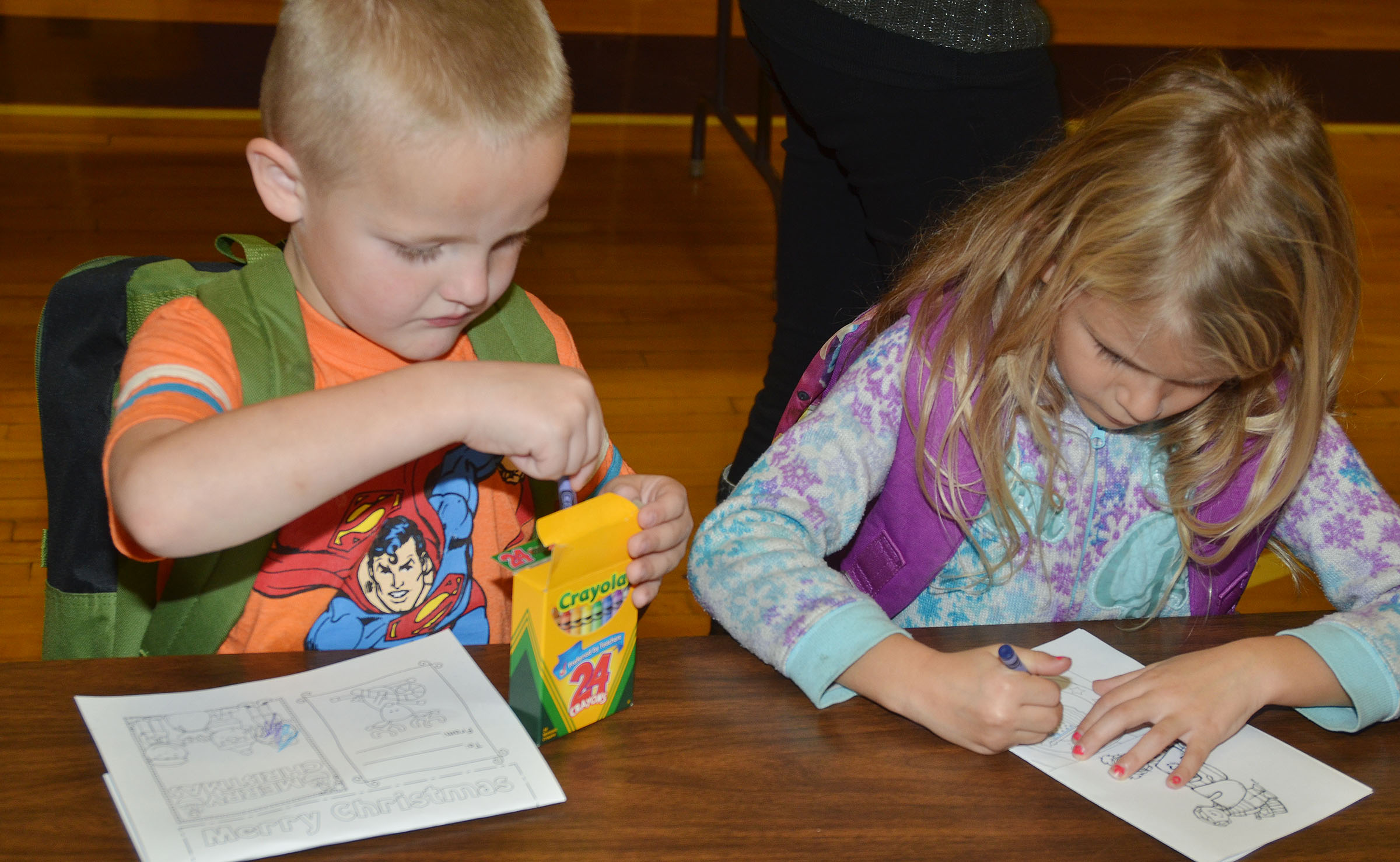 CES kindergarteners Tristian Harris and Gracelyn Gebler color cards for soldiers.