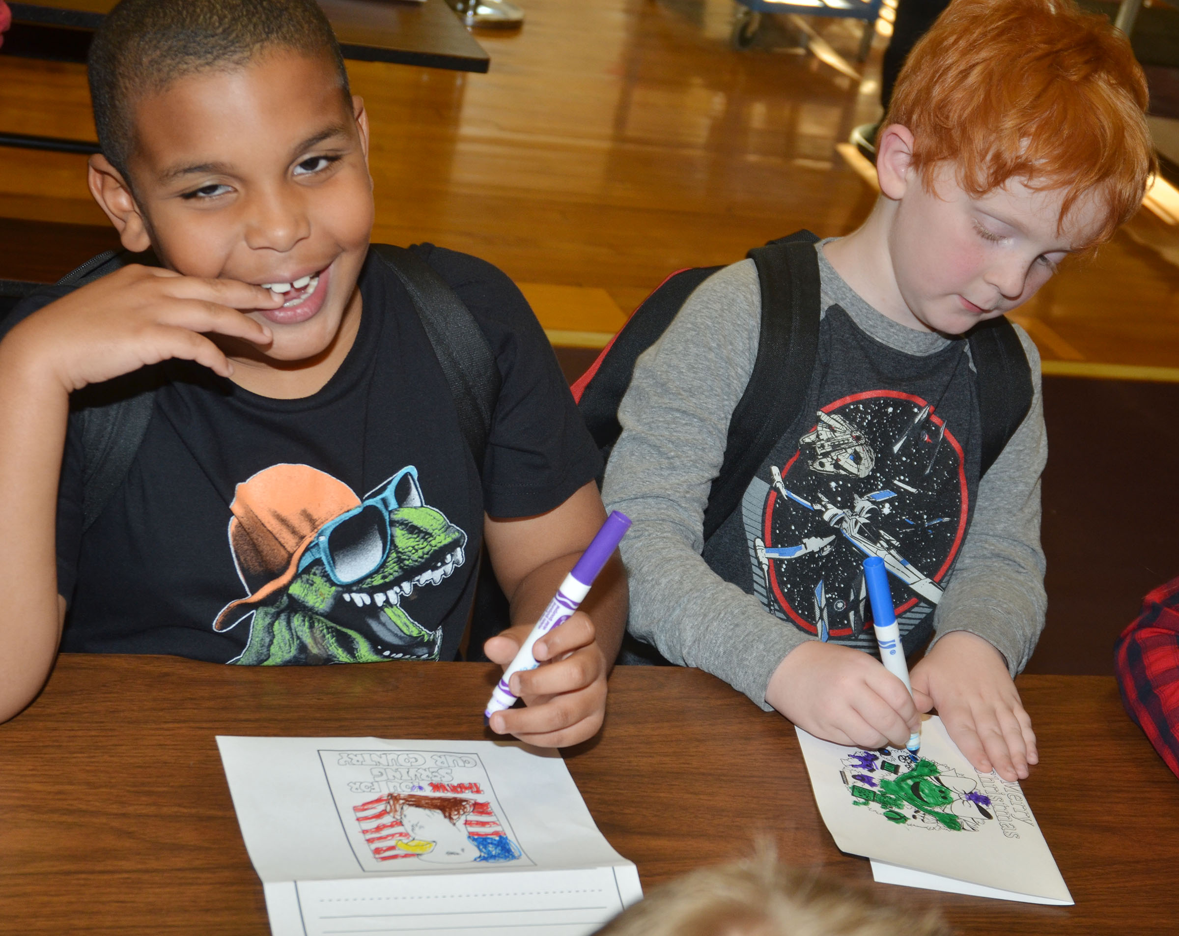 CMS second-graders Zaemar Hoskins, at left, and Gavin Martin color cards for soldiers.