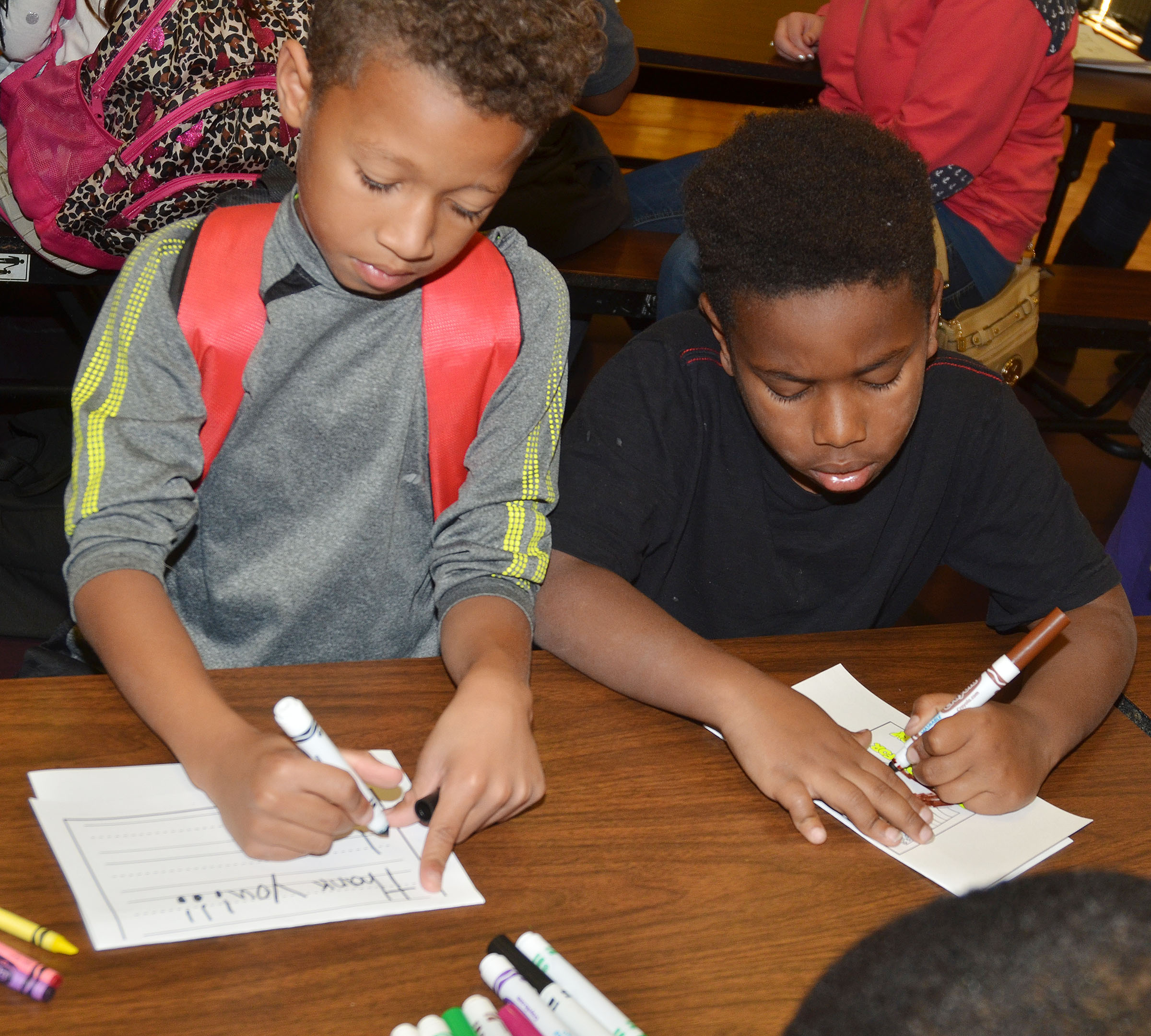 CMS second-graders Rajon Taylor, at left, and Elijah Spurling make thank you cards for soldiers.