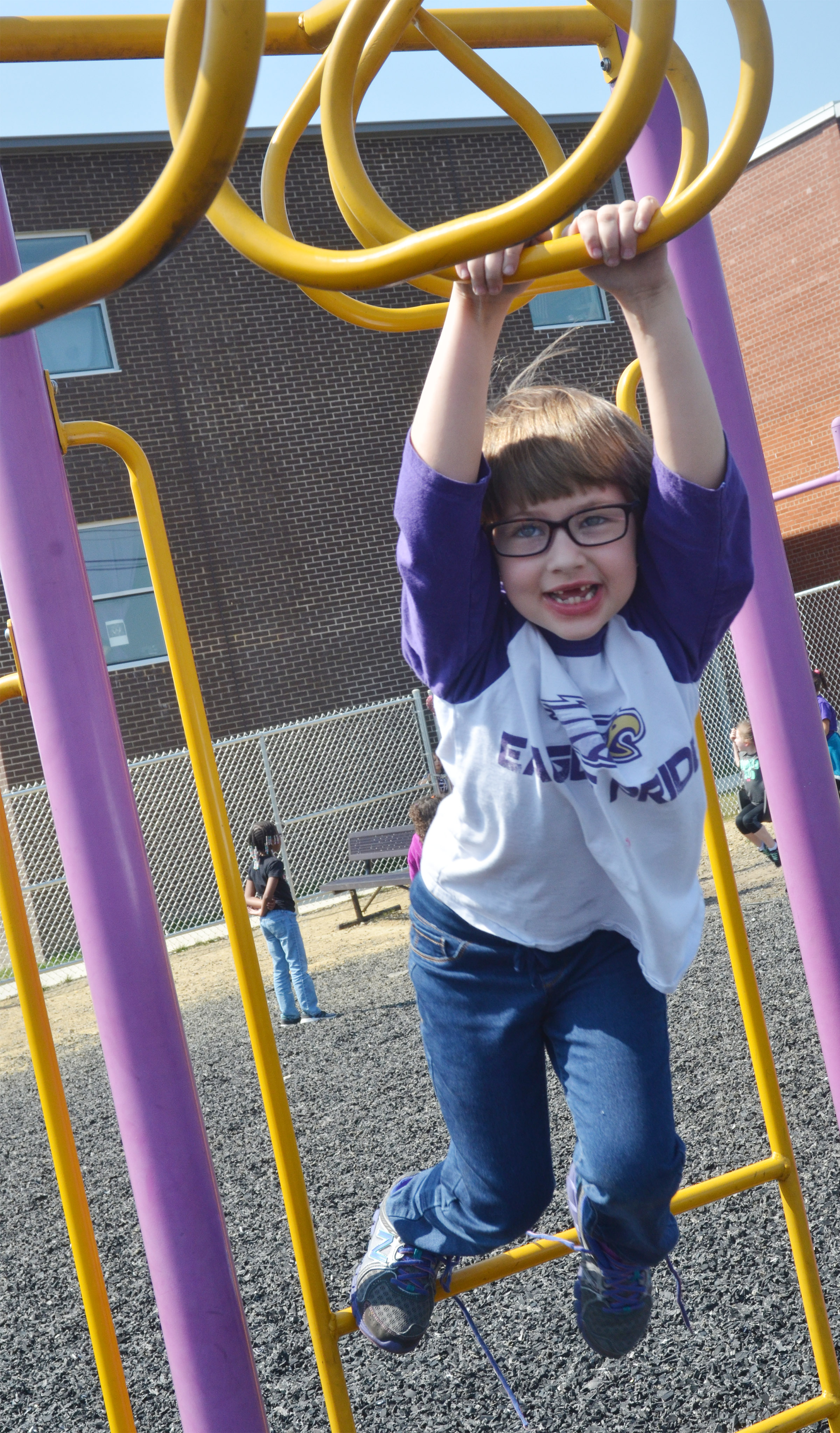 CES first-grader Addelyn Dooley hangs on the monkey bars.