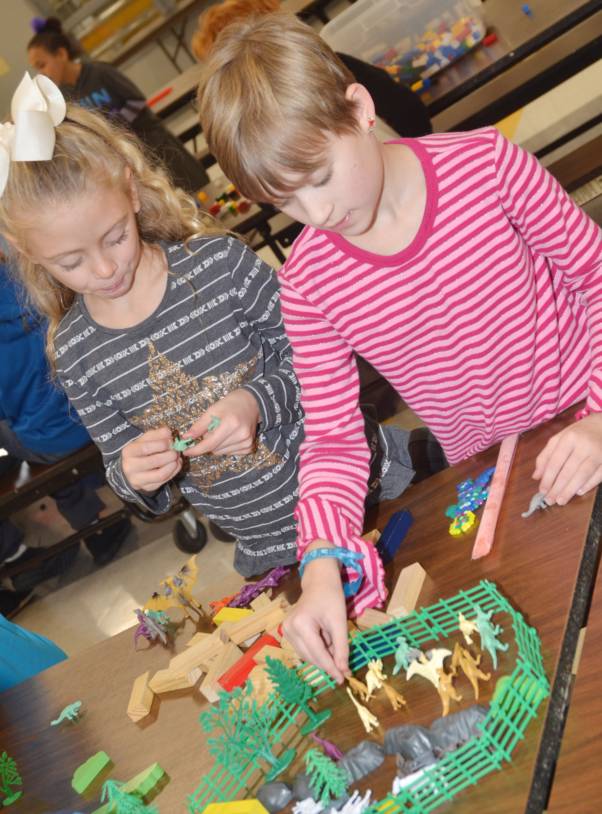 CES kindergartener Aliyah Litsey, at left, and third-grader Katie Nunn play with dinosaurs.