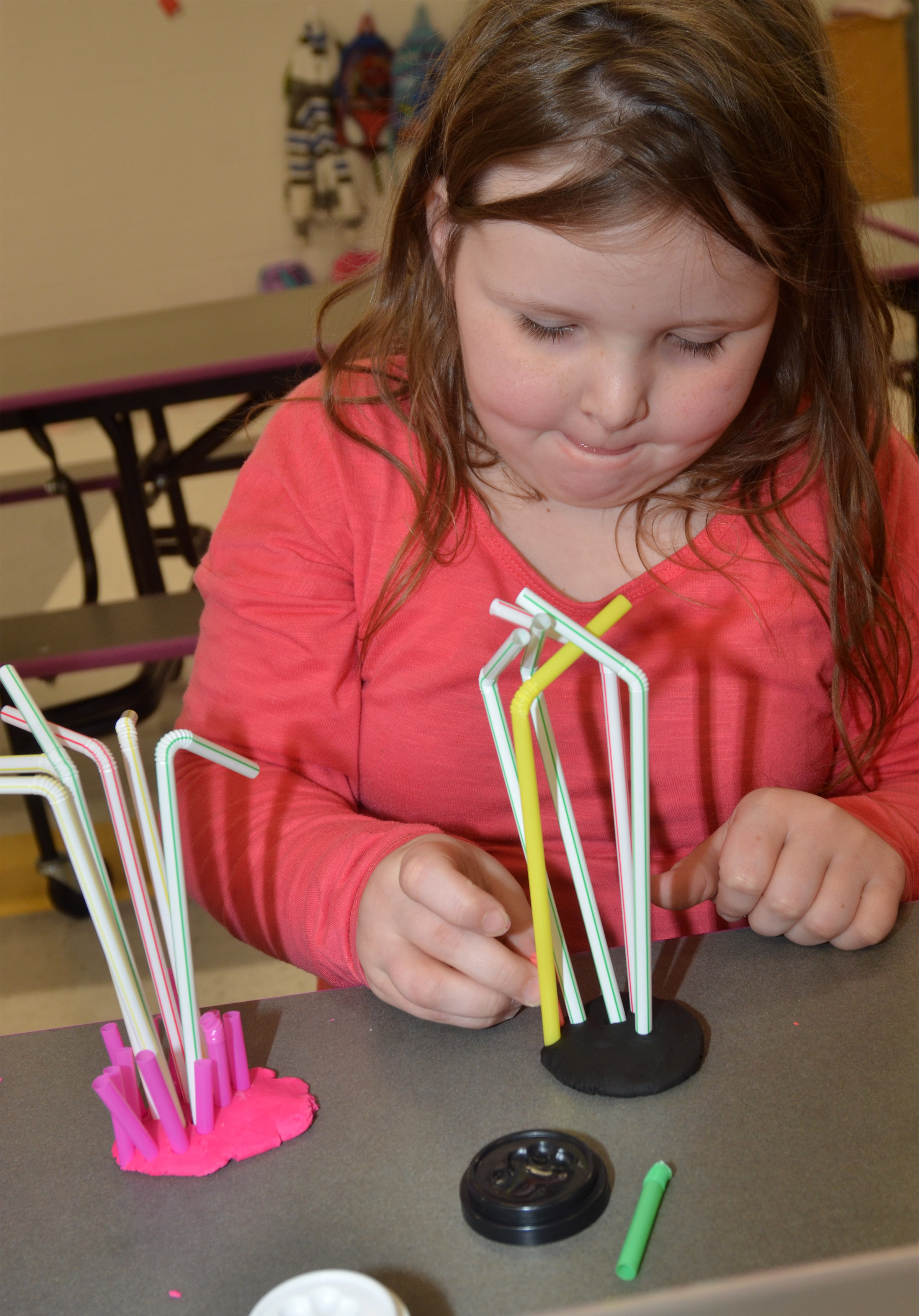 CES first-grader Kierra Maupin makes a sculpture out of Play-Doh and straws.
