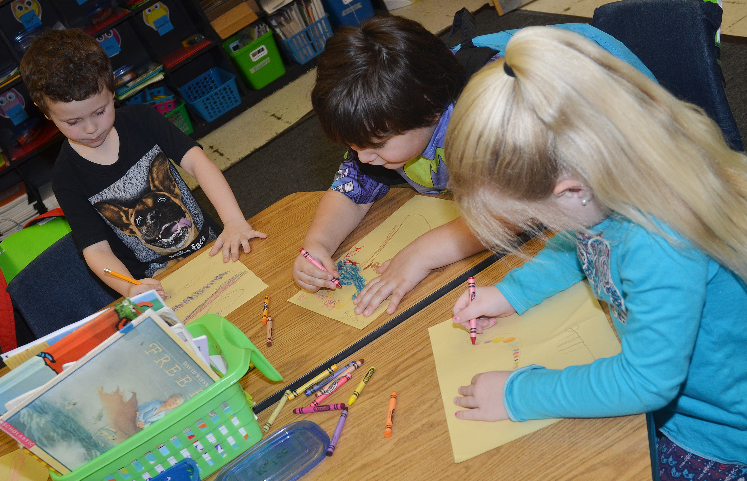 From left, CES kindergarteners Brayden Perkins, Cloud Malone and Lillie Judd color their snakes.