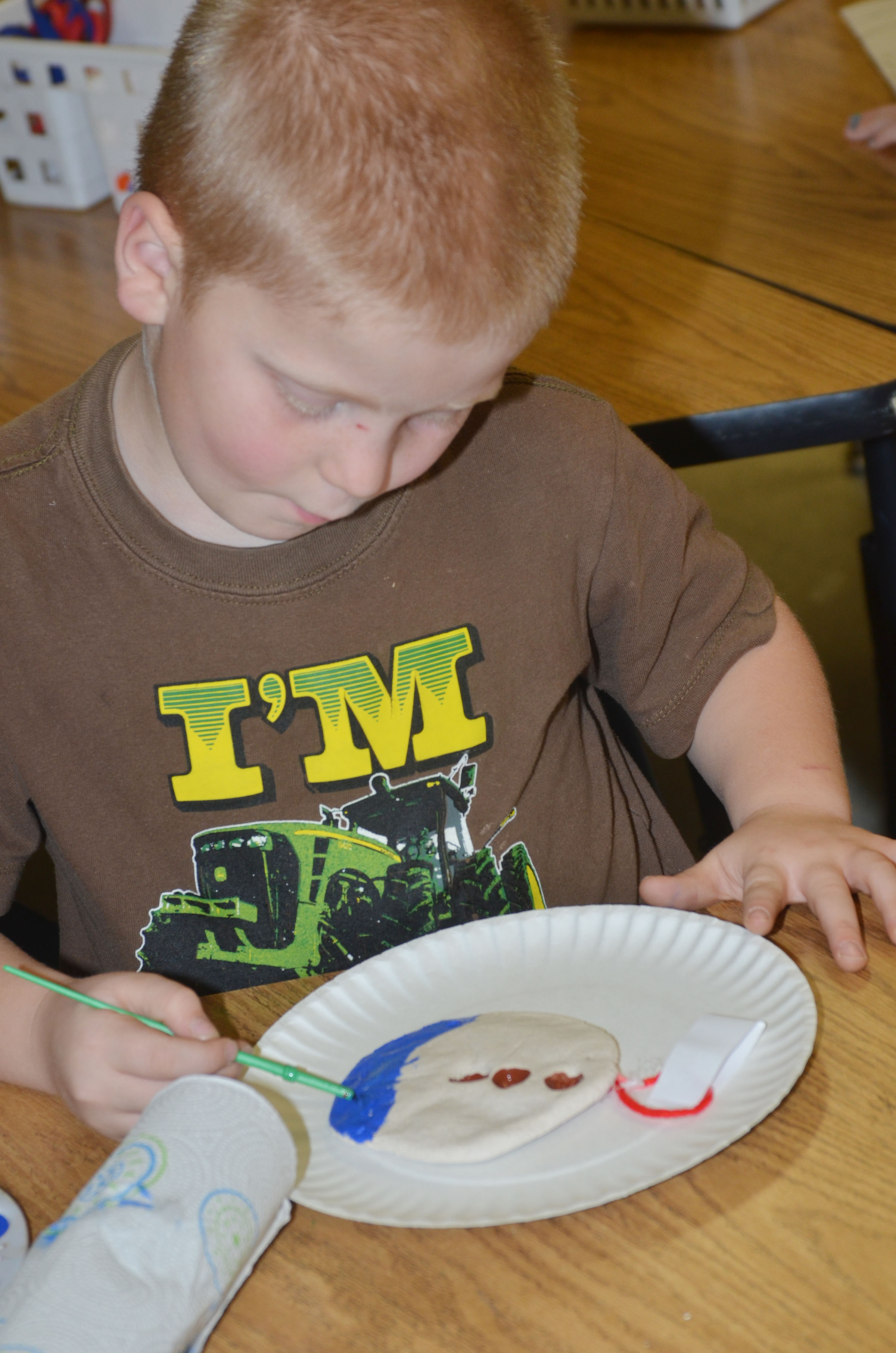 CES first-grader Ben Parrott paints his salt dough ornament.