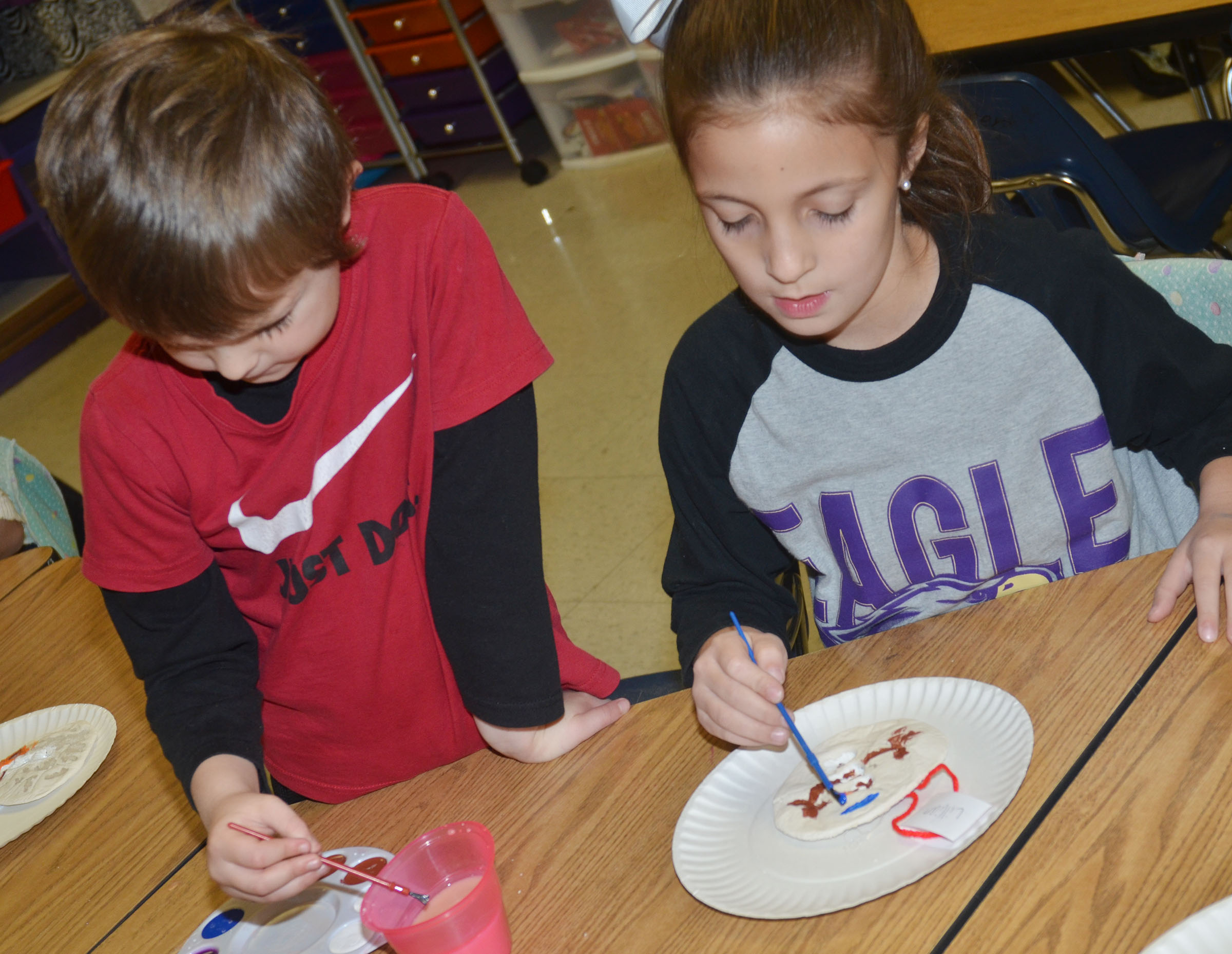 CES first-graders Karson Burchett, at left, and Lillian Martin paint their salt dough ornaments.
