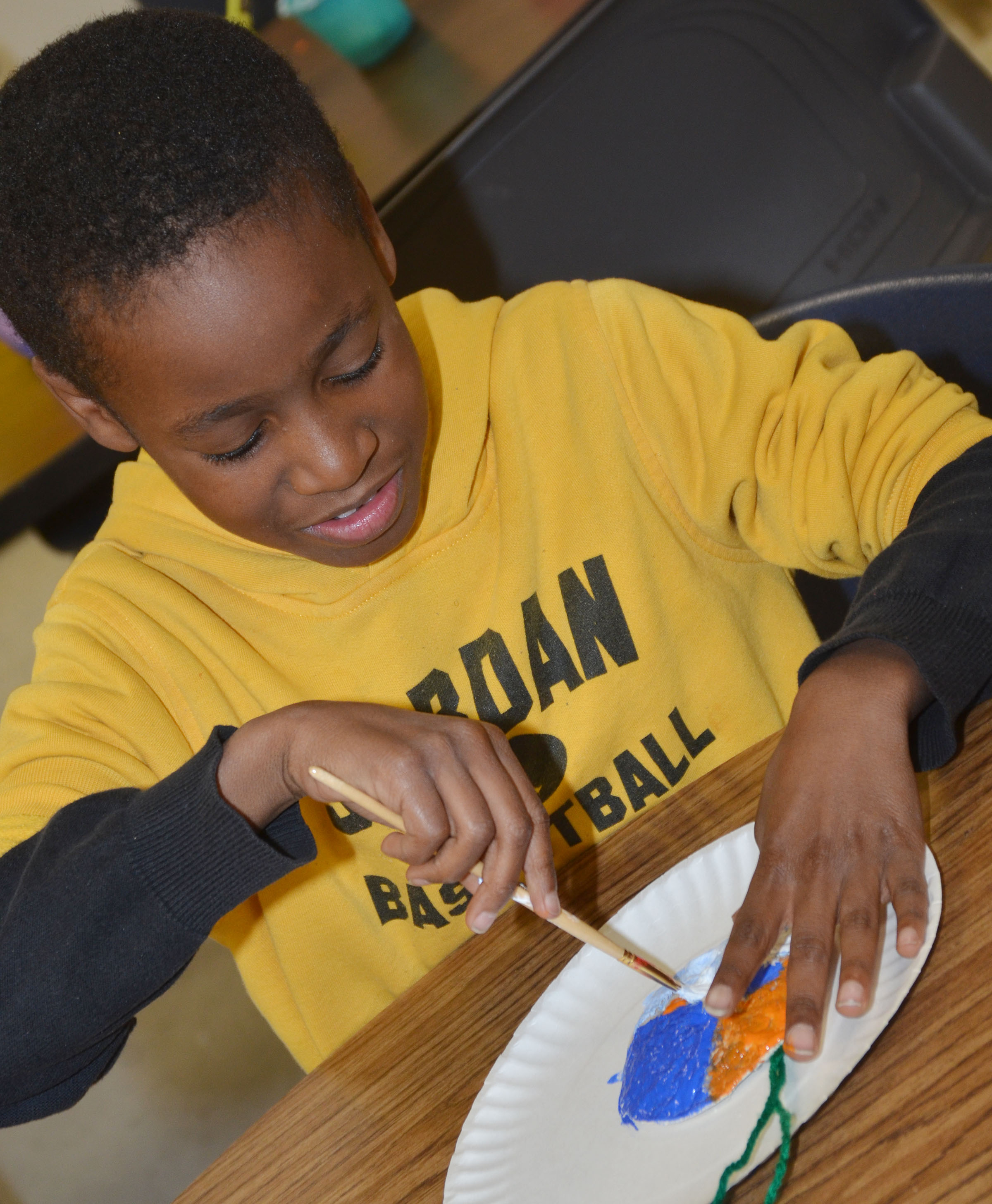 CES third-grader John Gholston paints his salt dough ornament.