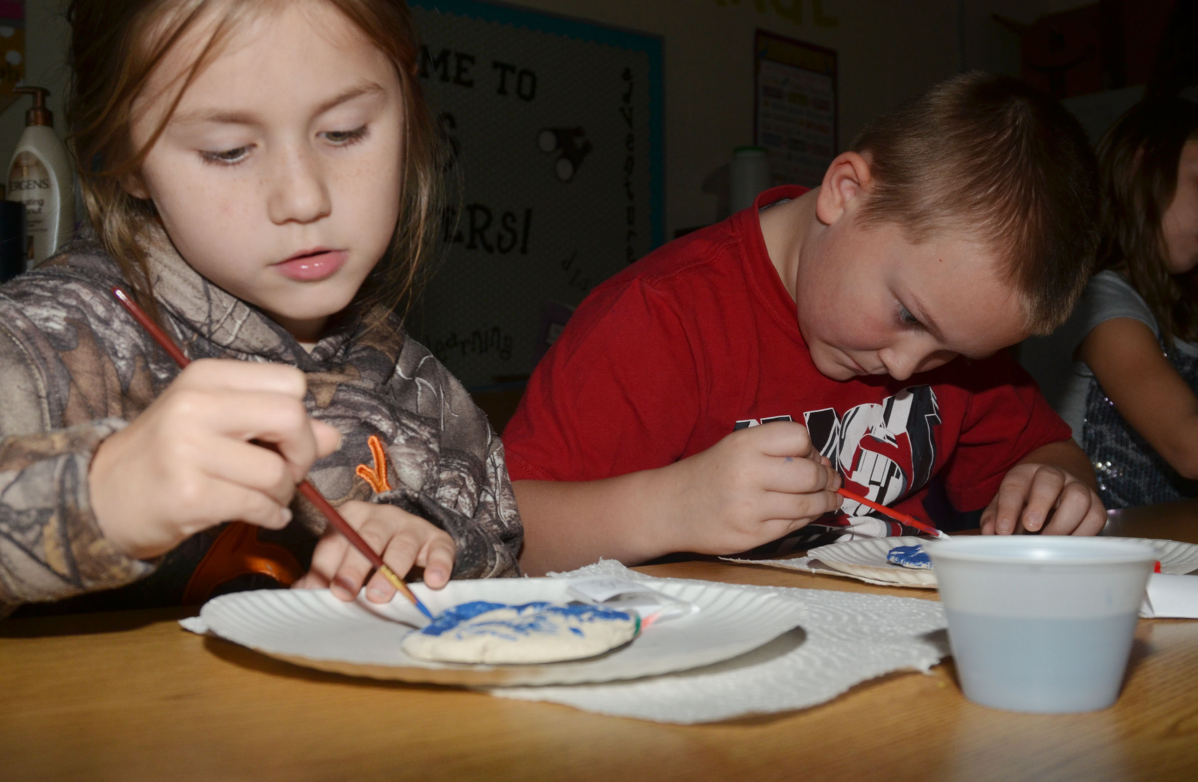 CES second-graders Bryleigh Curry, at left, and Griffin Skaggs paint their salt dough ornaments.