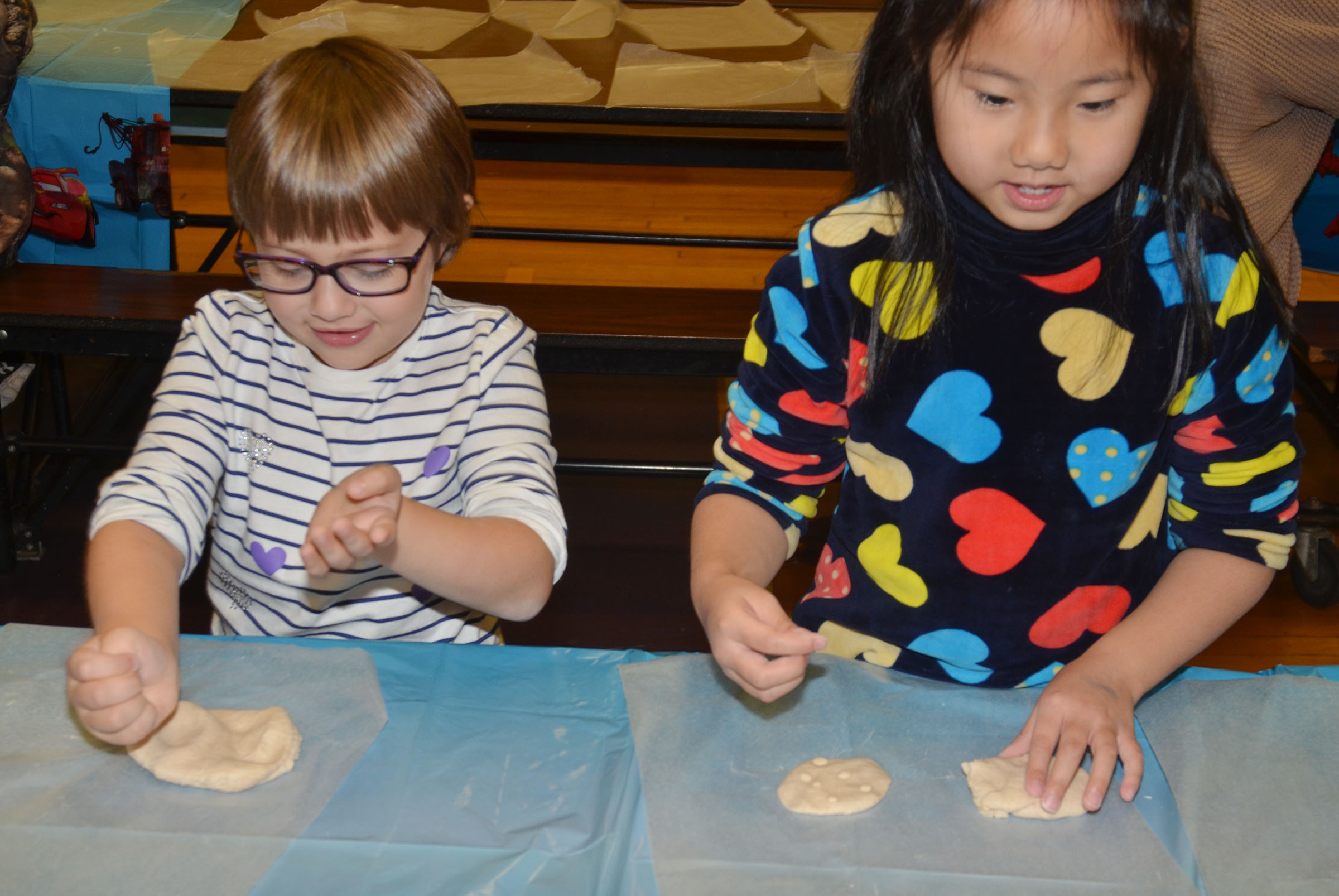CES first-graders Addelyn Dooley, at left, and Tina Jiang smooth their salt dough into ornaments.