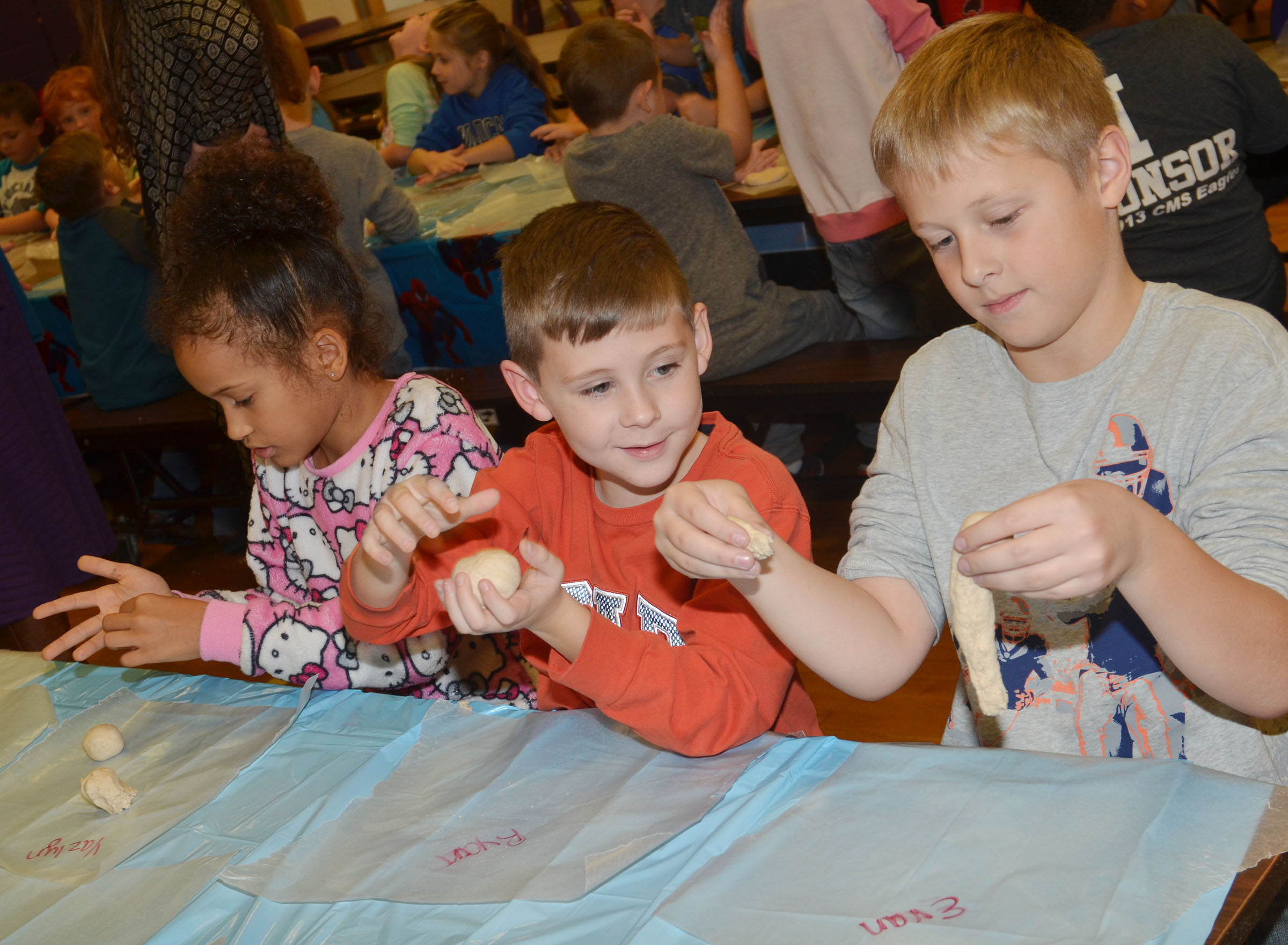 From left, CES second-graders Yazlyn Sutton, Ryan Tungate and Evan Lockridge make their salt dough ornaments.