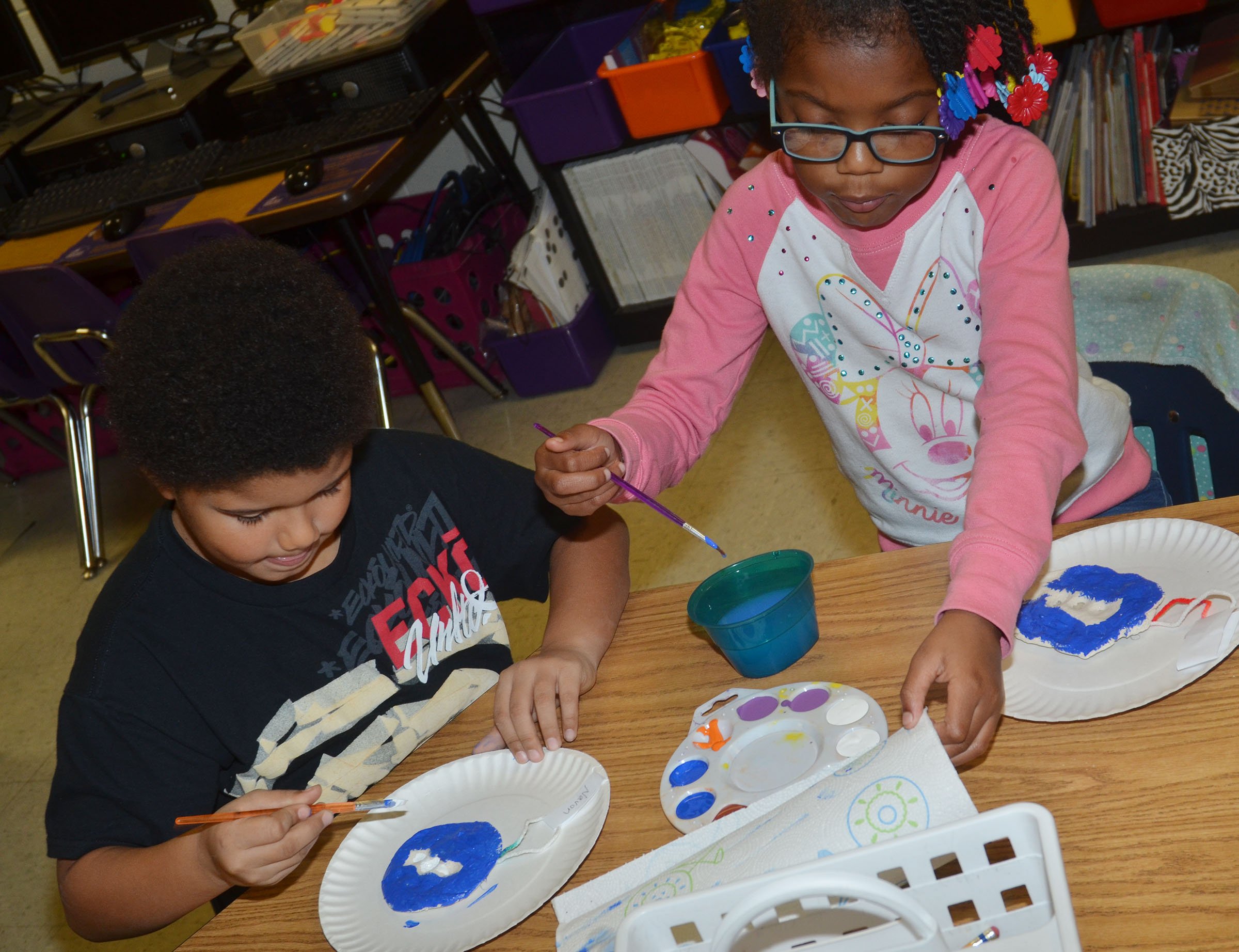 CES first-graders Navon Copeland, at left, and Willow Griffin paint their salt dough ornaments.