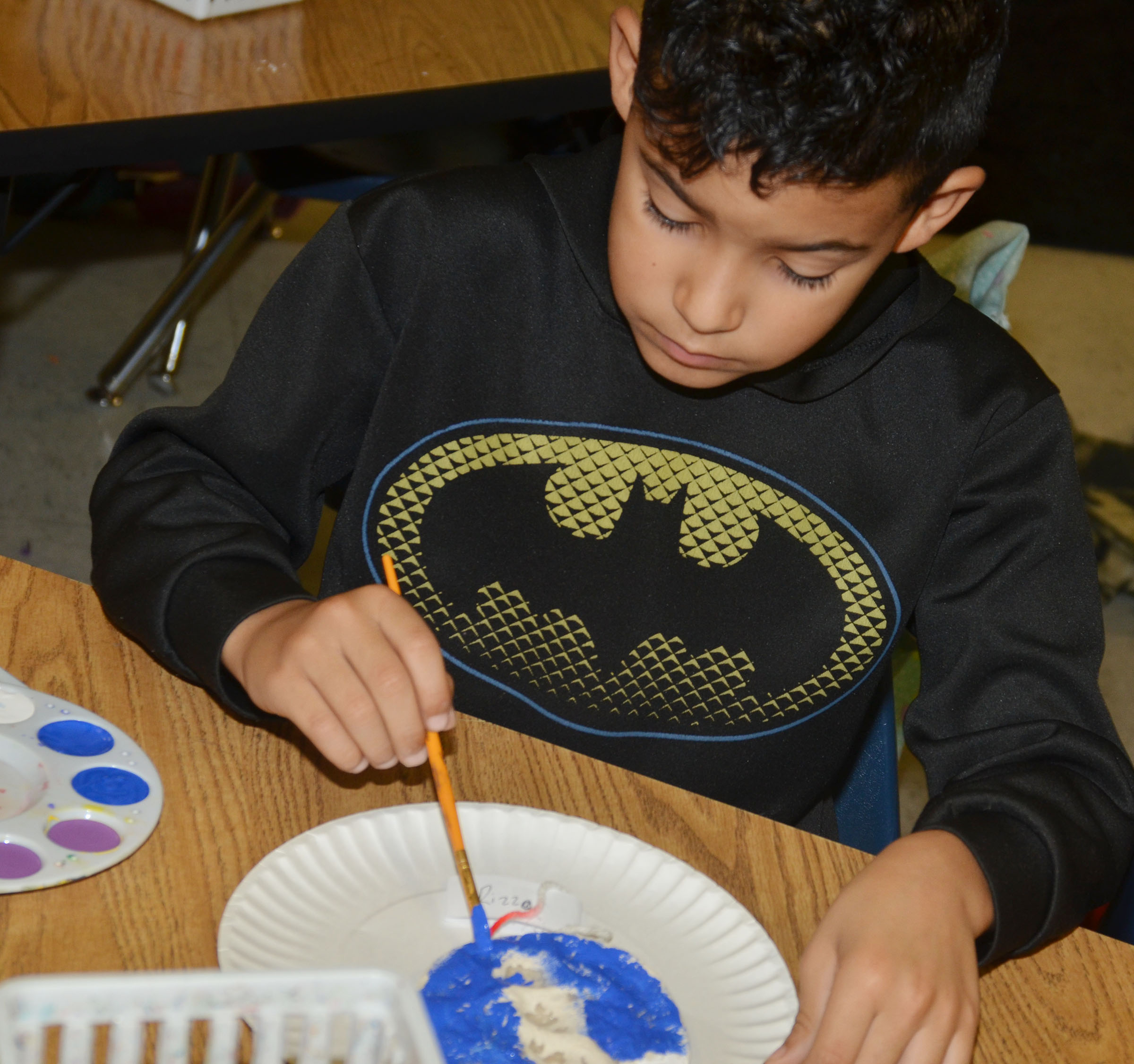 CES first-grader Rizzo McKenzie paints his salt dough ornament.