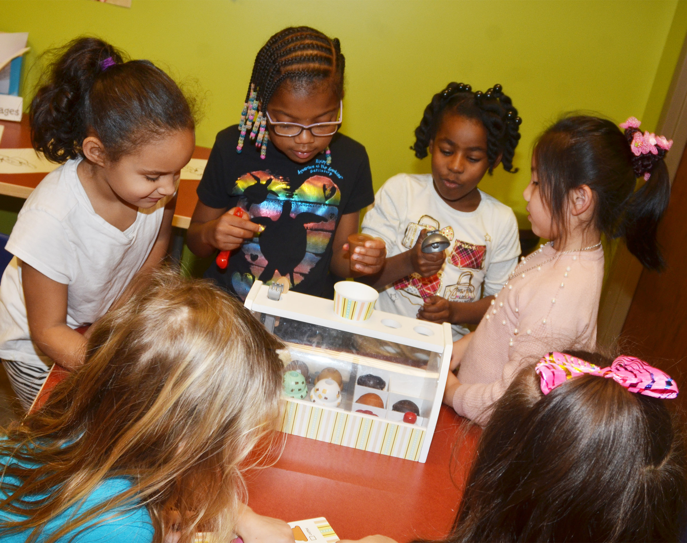 From left, CES first-graders Amani Bridgewater, Willow Griffin, Destini Gholston and Tina Jiang operate an ice cream stand for their friends at the library.