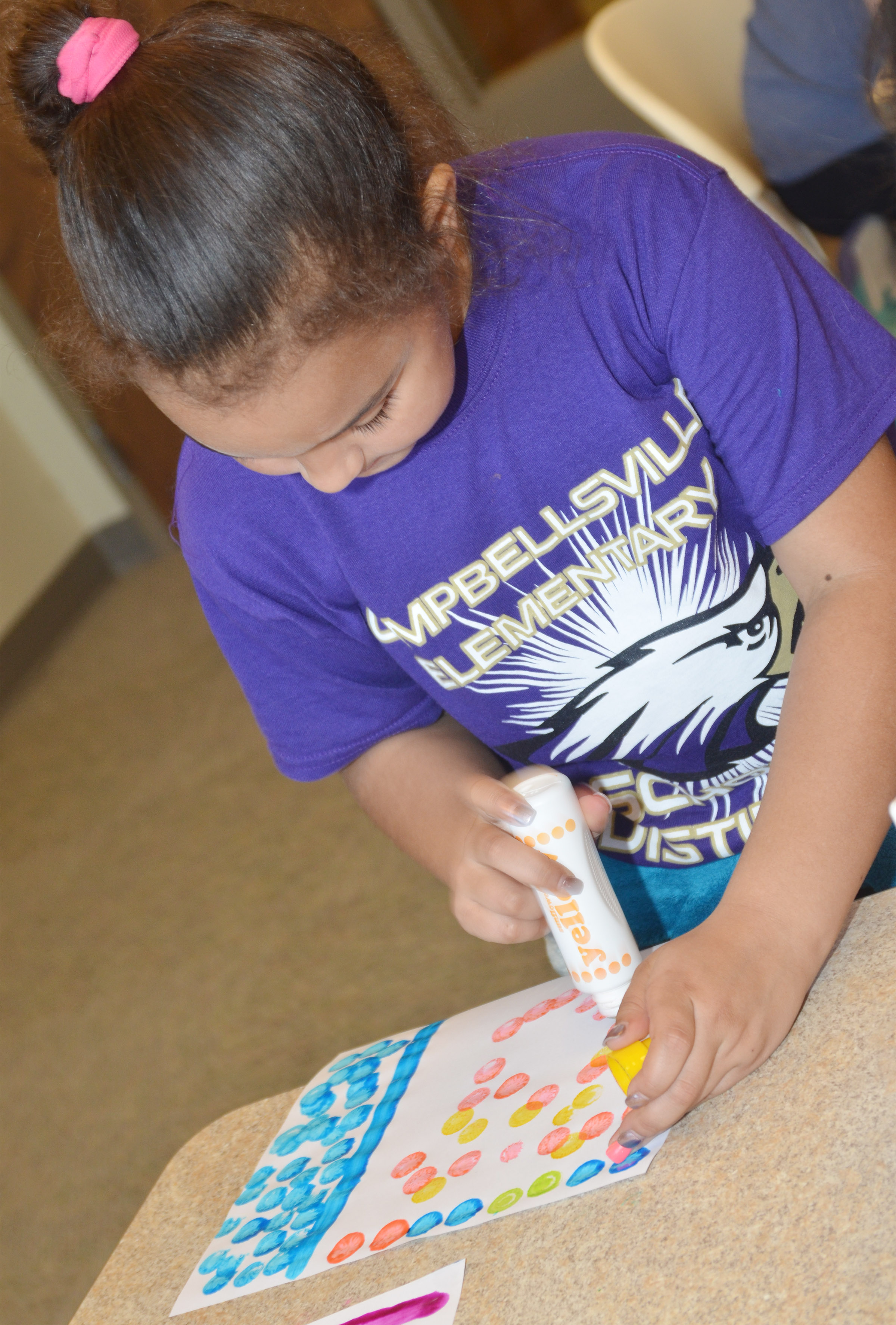 CES first-grader Maleigha Travis paints at the library.