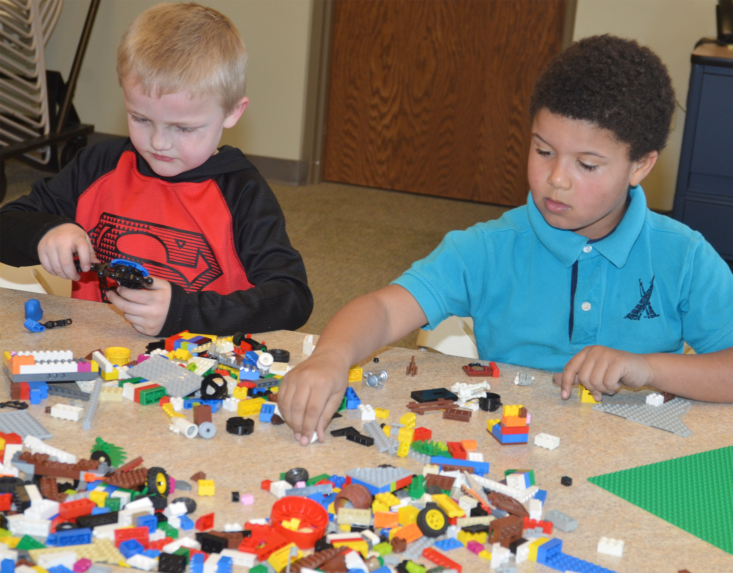 CES kindergartener Tristian Harris, at left, and first-grader Navon Copeland build with Legos at the library.
