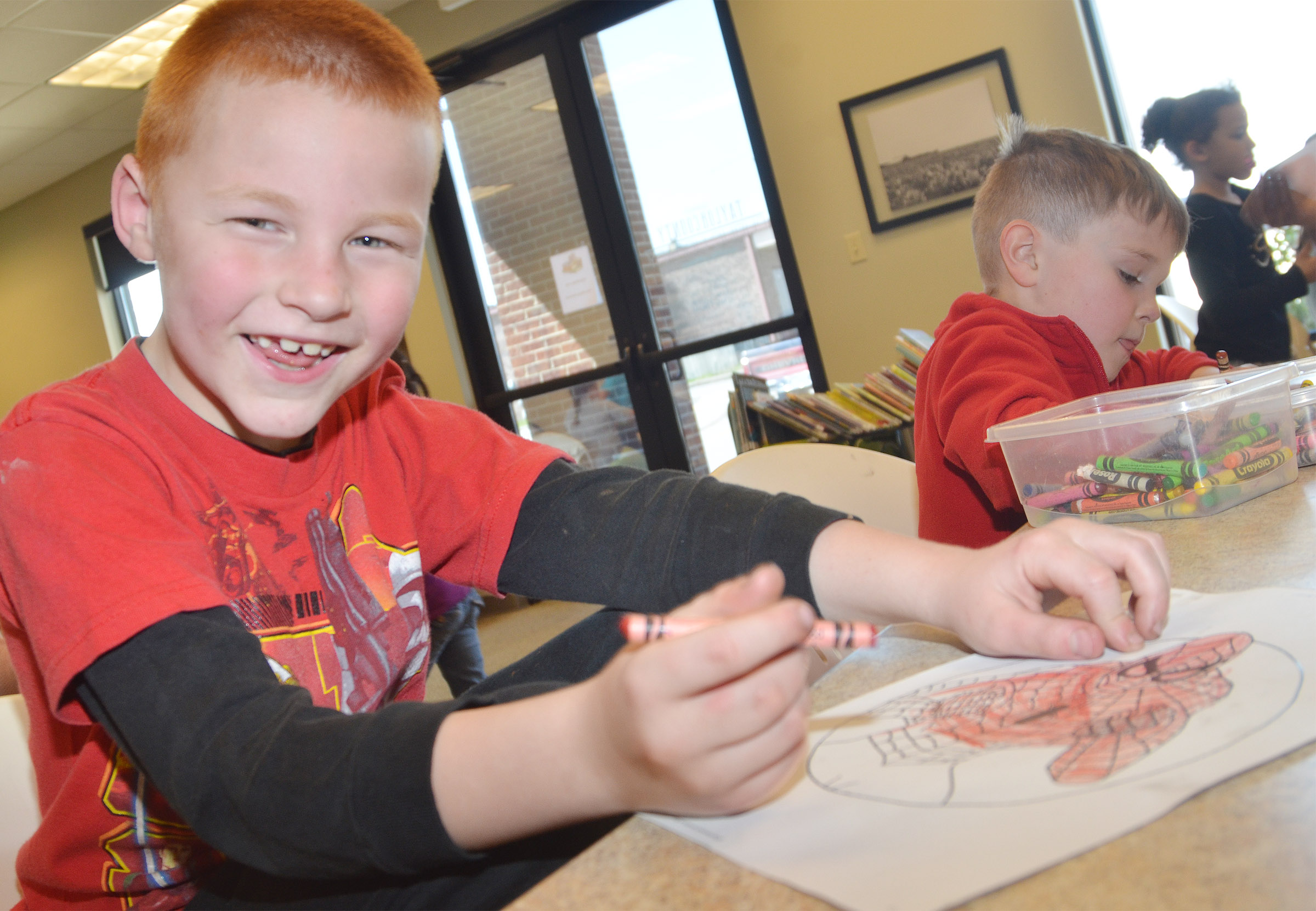 CES first-grader Carter Wethington smiles as he colors at the library.