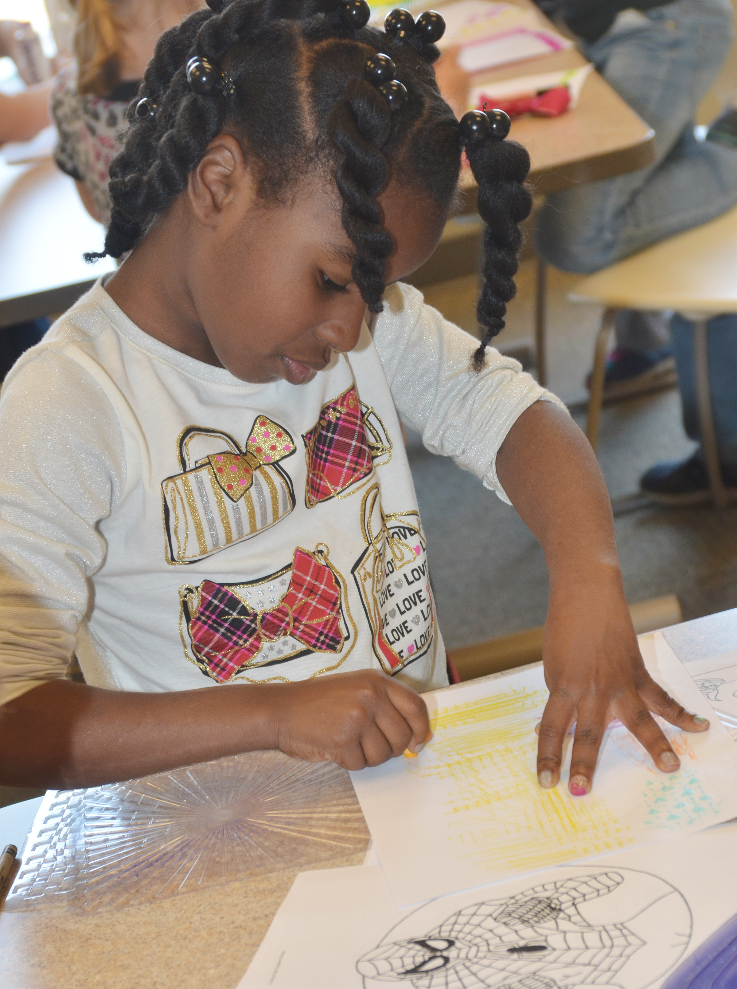 CES first-grader Destini Gholston colors at the library.