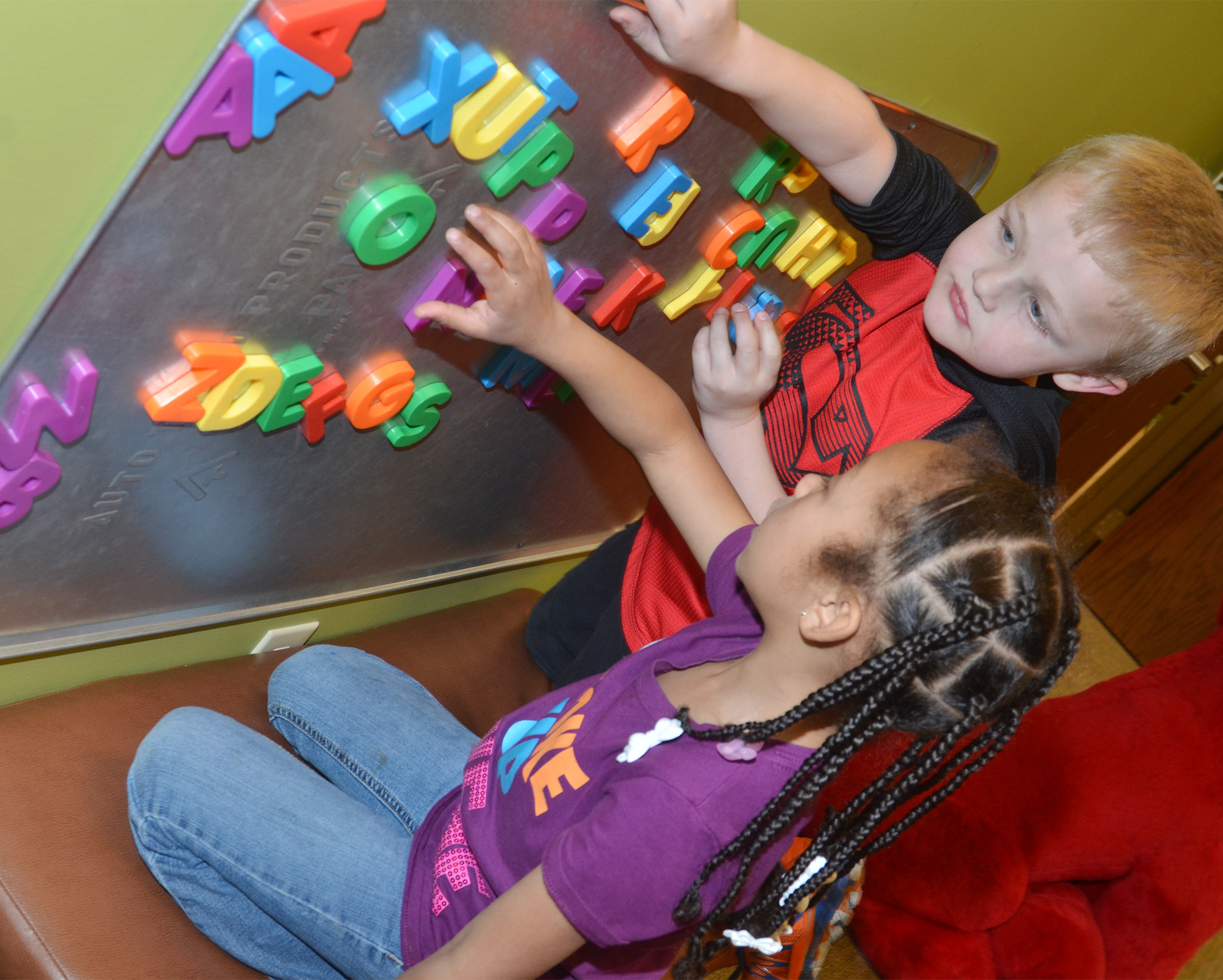 CES kindergarteners Elyzabeth Fisher and Tristian Harris spell with magnets at the library.