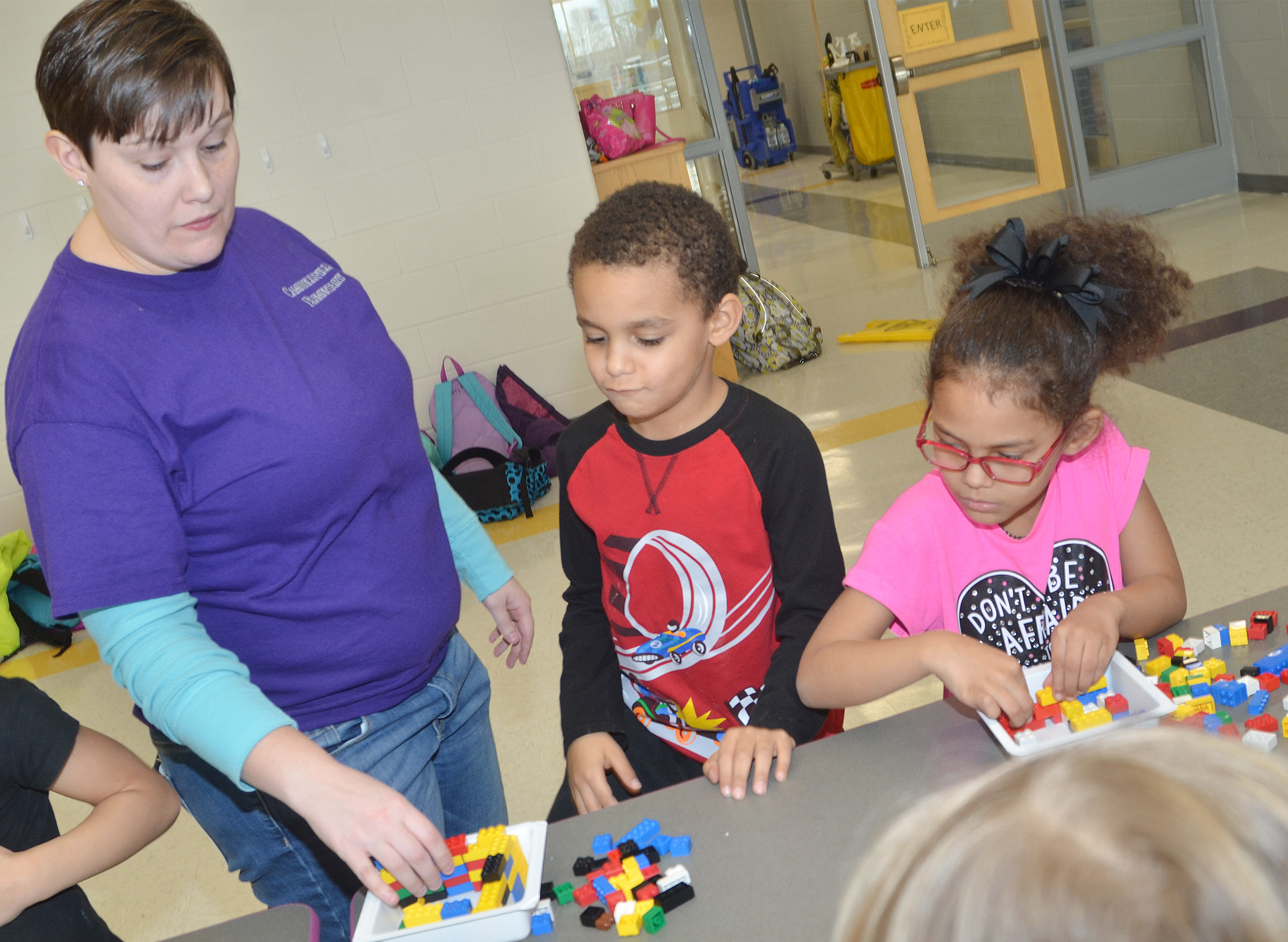 CES Wings Express Director Amanda Barnett helps kindergartener Quincy Travis build his Lego volcano.
