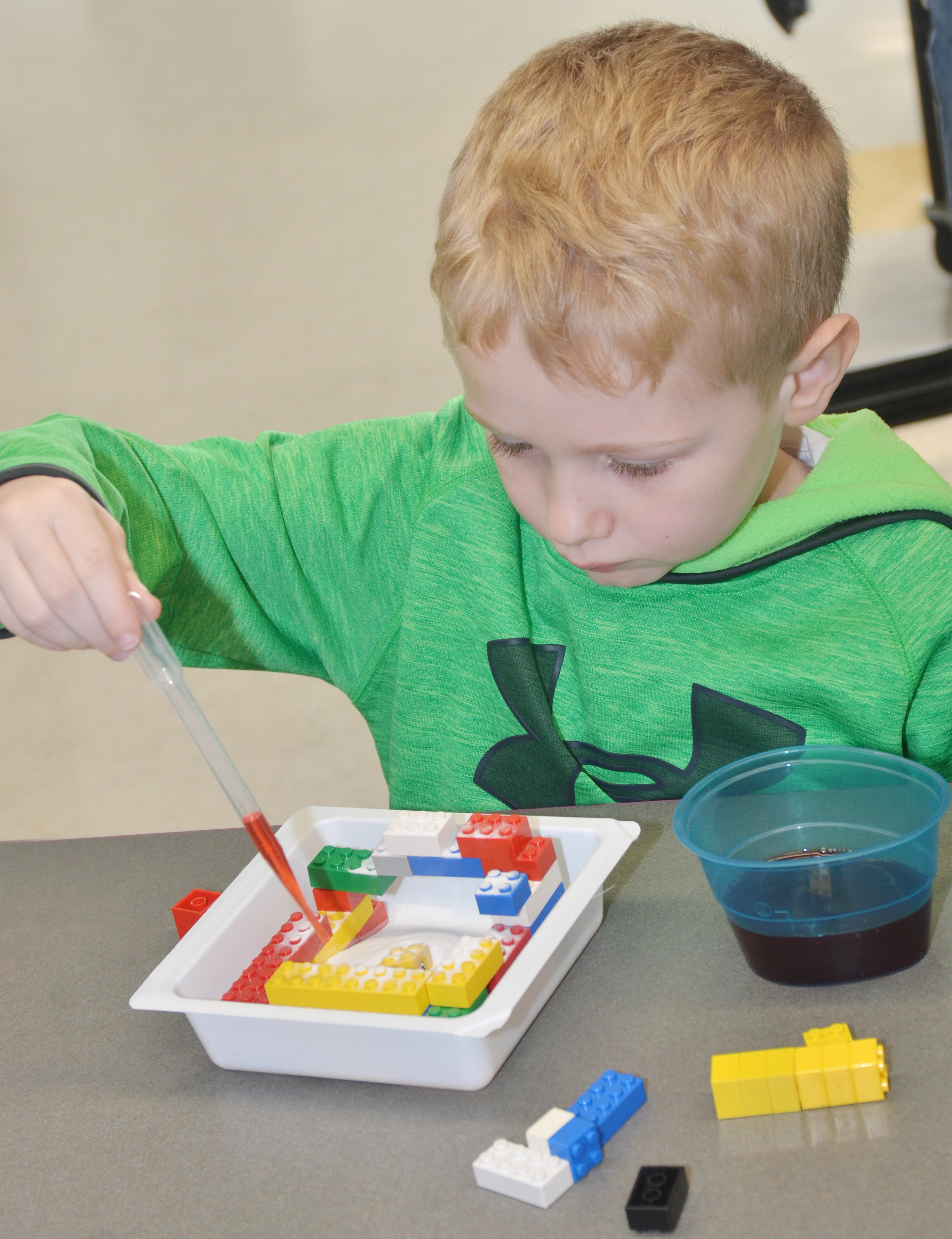 CES kindergartener Jackson Wright drops vinegar on his Lego volcano.