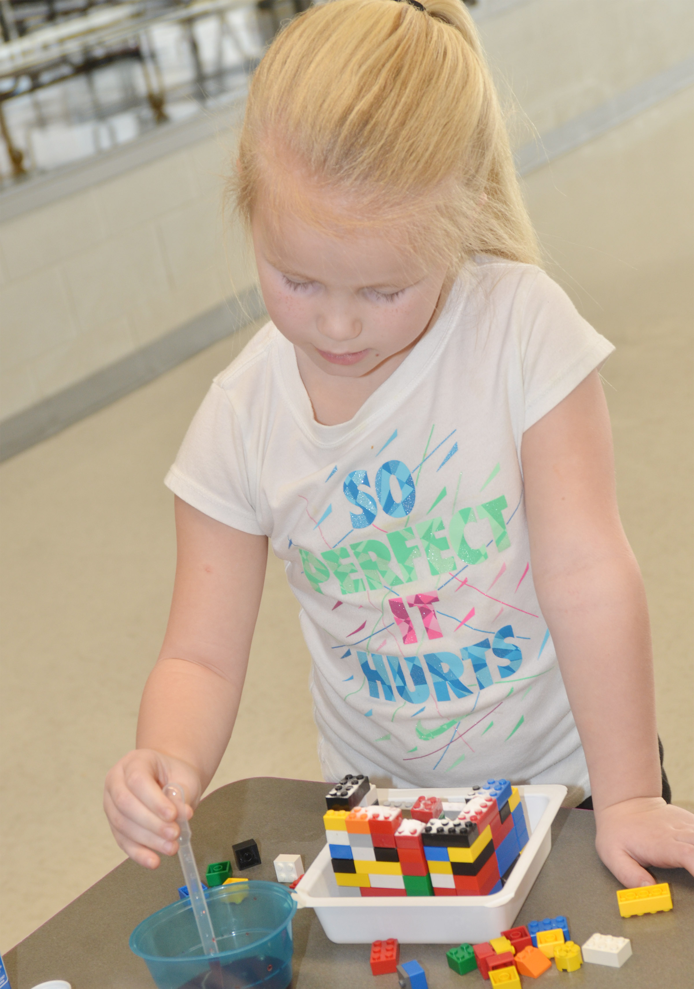 CES kindergartener Lillie Judd drops vinegar on her Lego volcano.