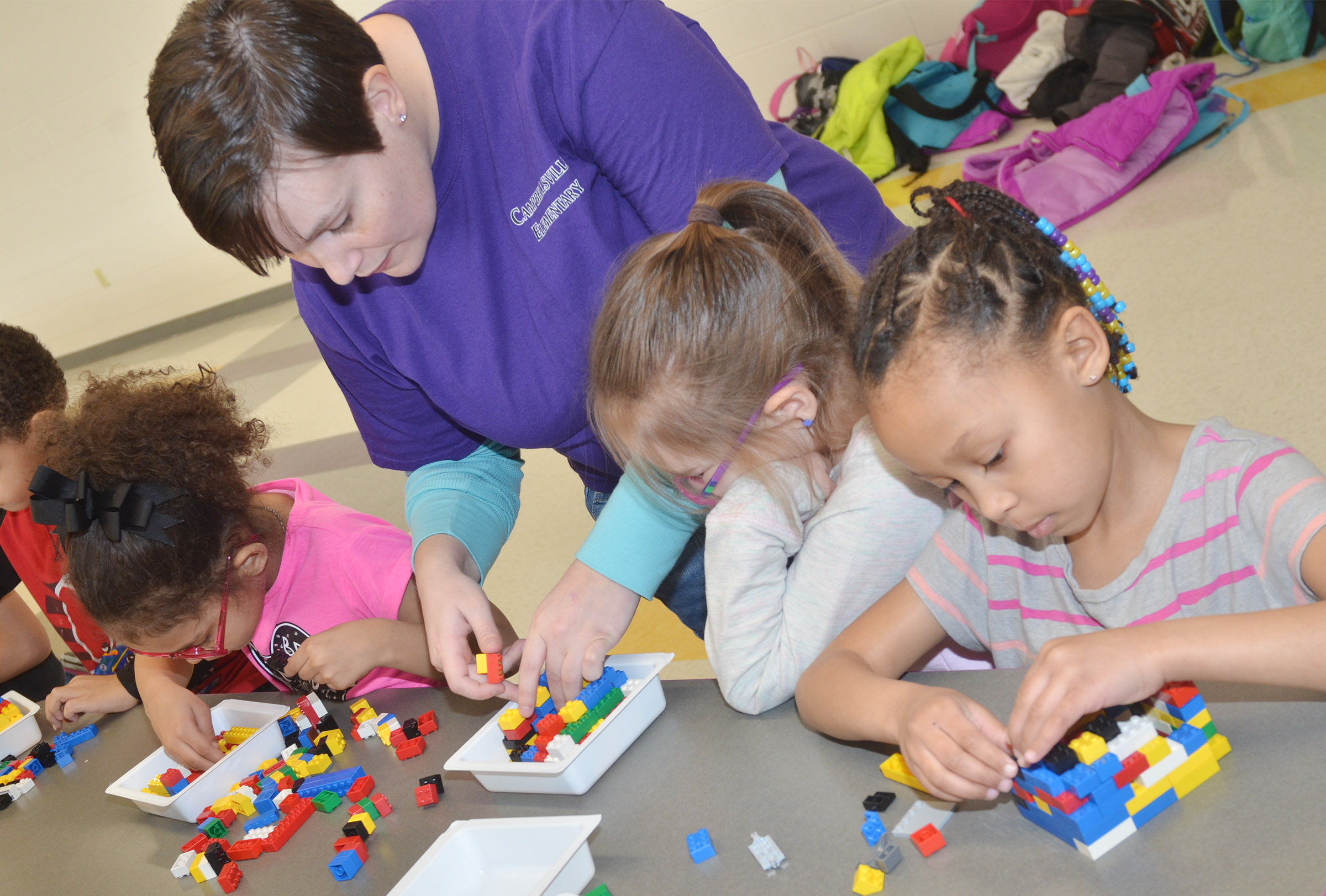 CES Wings Express Director Amanda Barnett helps kindergartener Aubrey Allen build her Lego volcano.