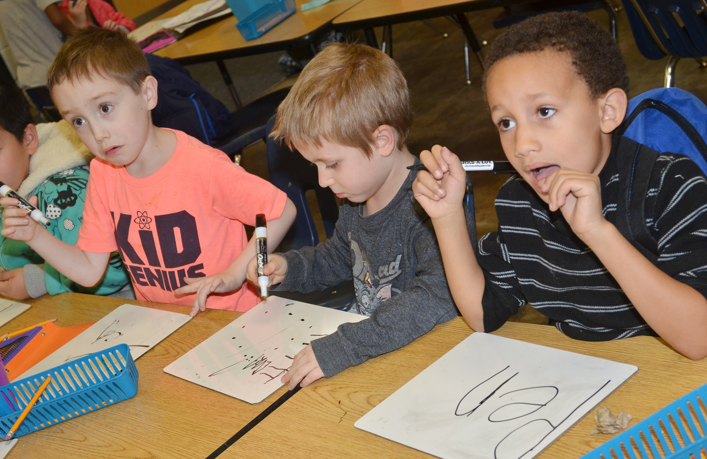 CES kindergarteners, from left, Joshua Dickens, Alex Newcomb and Jaxon Williams practice writing their sight words.