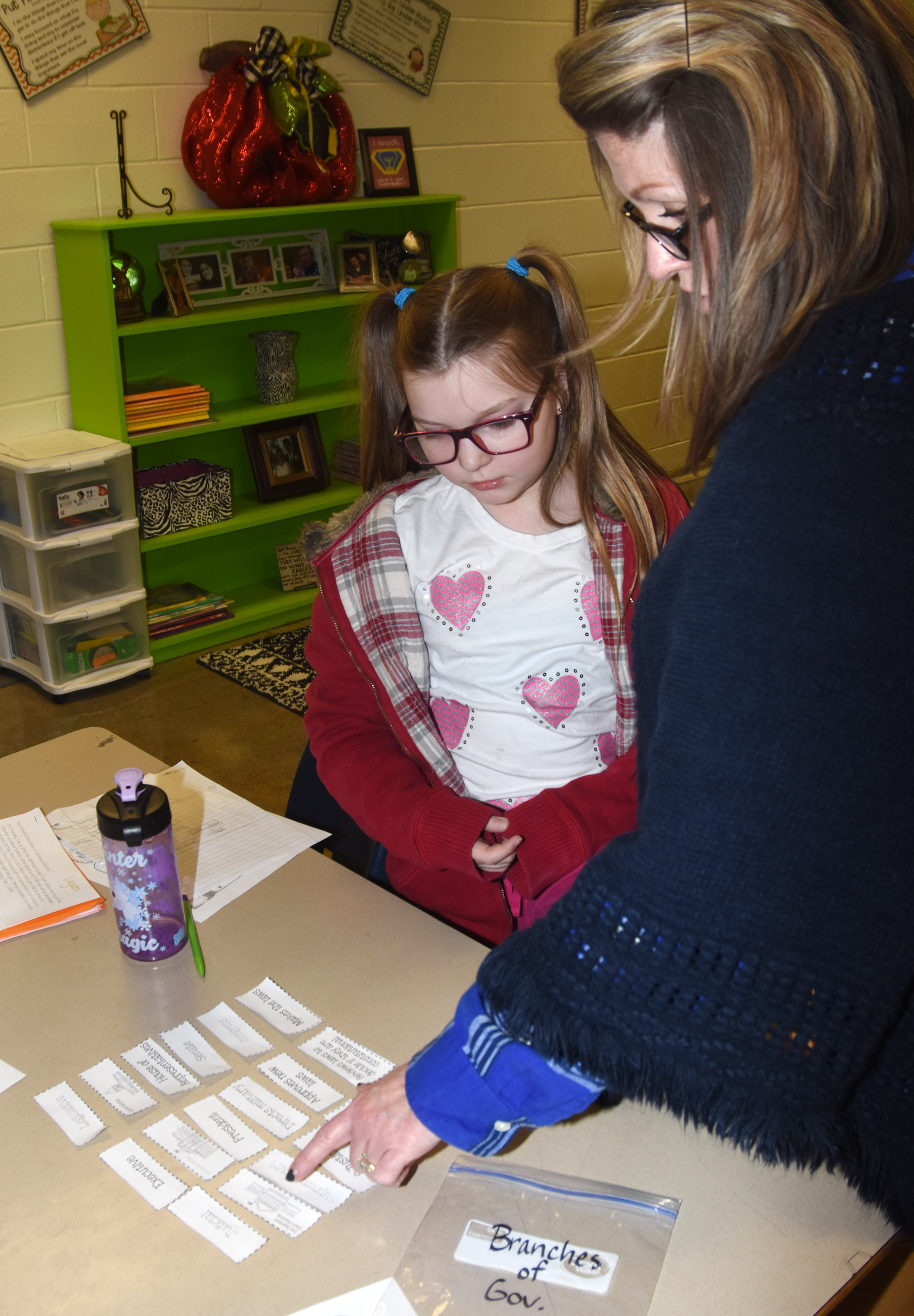 CES fifth-grade teacher Donna White helps Morgan Spears complete a branches of government card sort game.