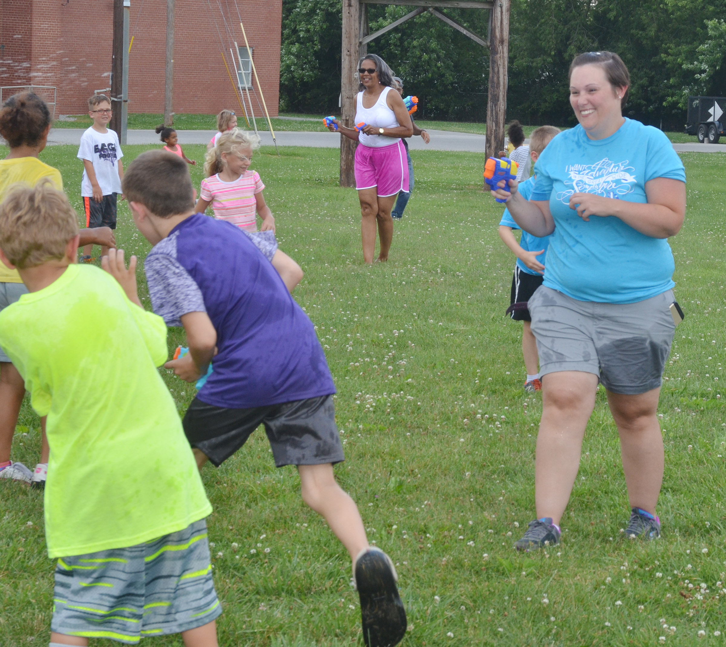 CES Wings Express Director Amanda Barnett sprays her students with a water gun.