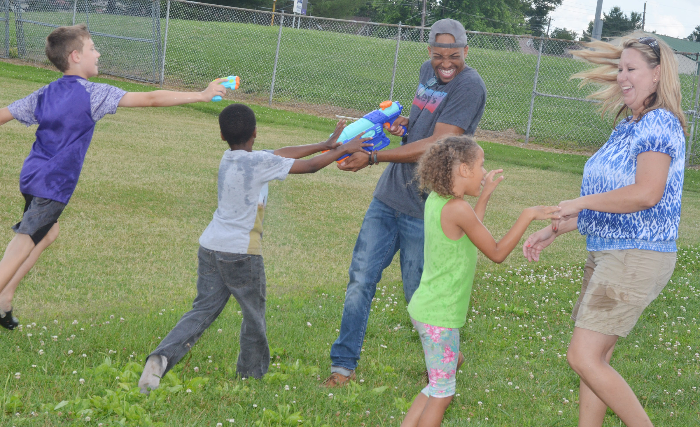 CES Wings Express students spray assistants George Boyd, at left, and Amanda Greer with water guns.