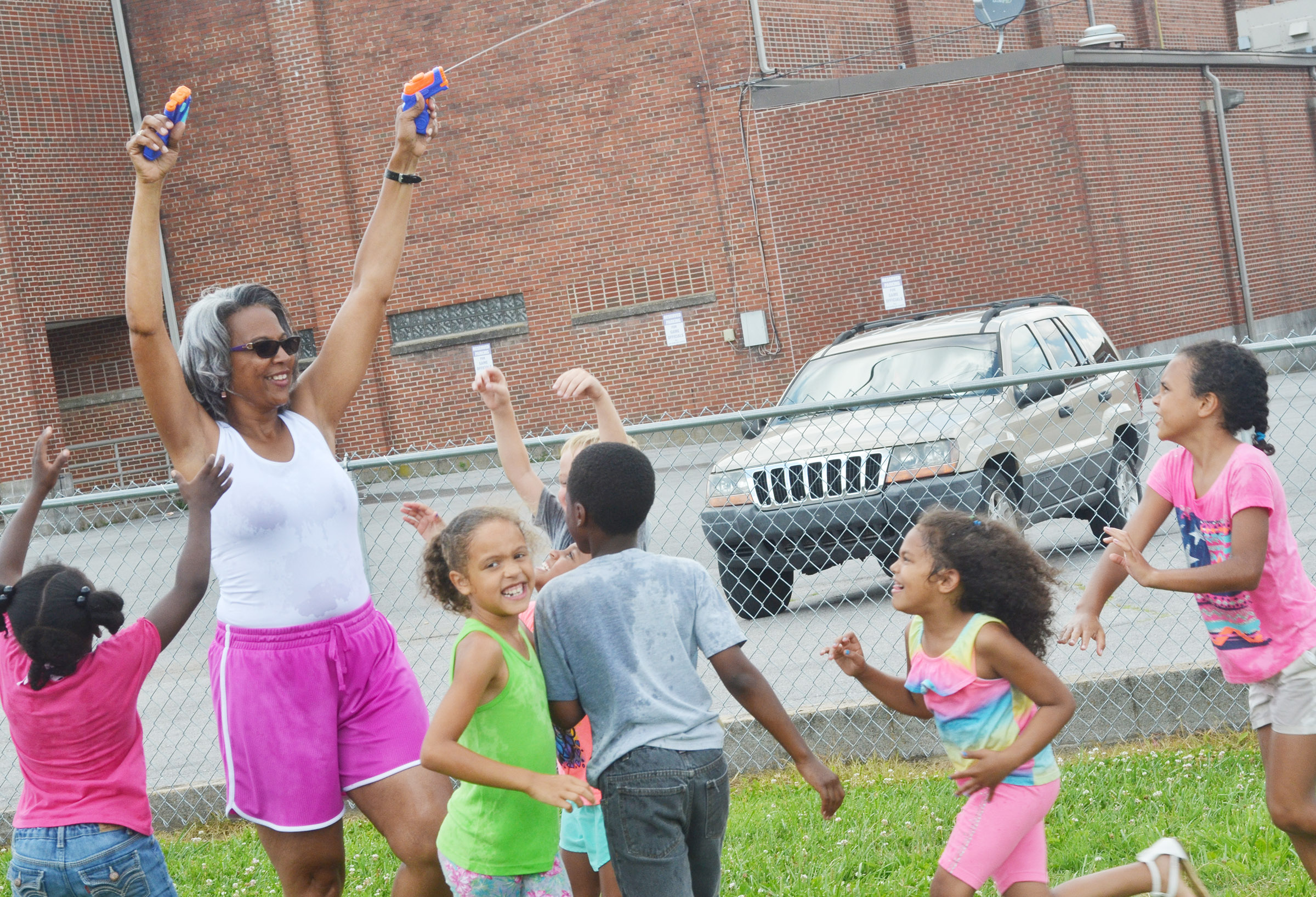 CES Wings Express assistant Doretha Sanders sprays her students with water guns.
