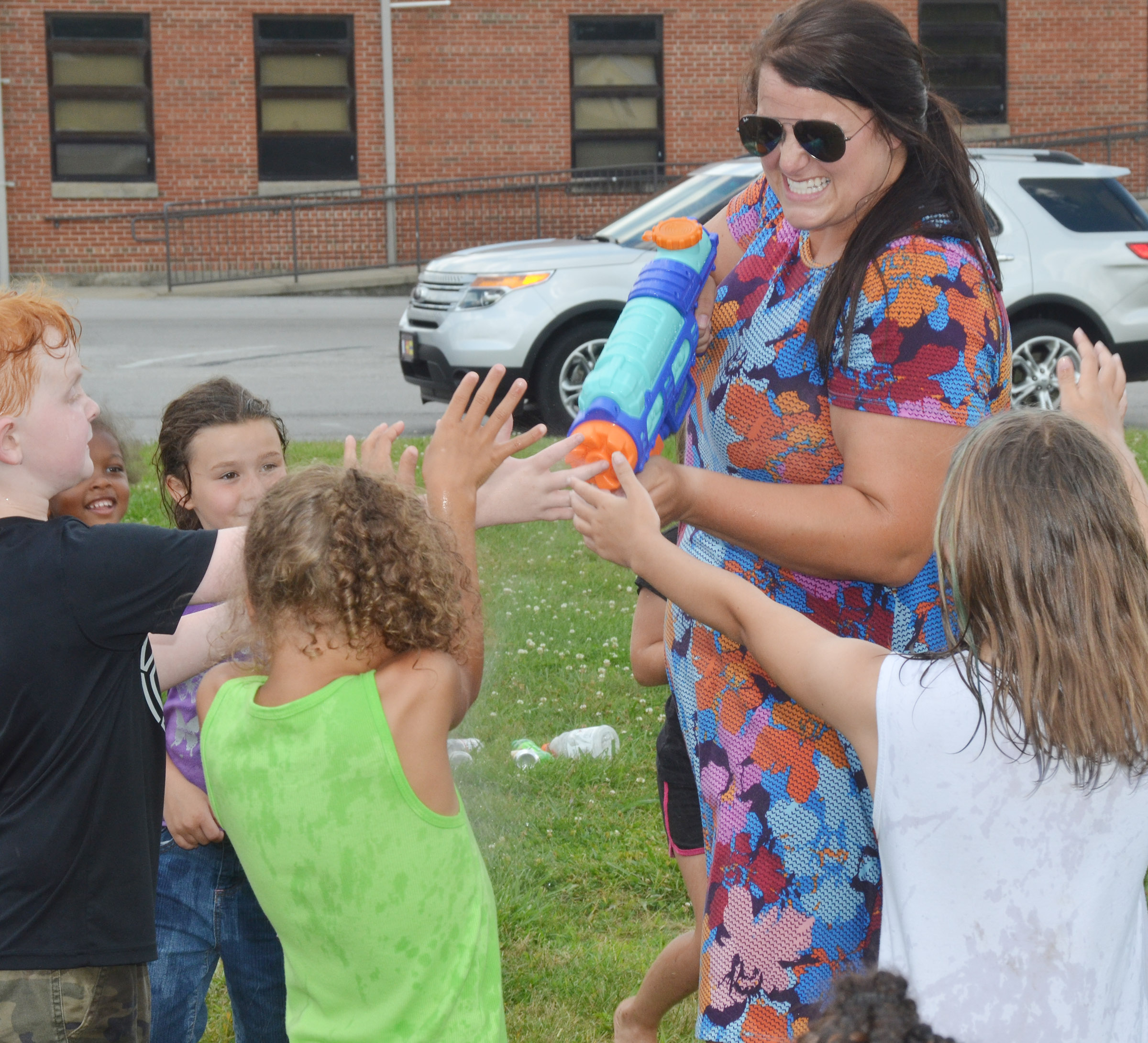 CES Wings Express assistant Miriah Cox sprays her students with water guns.