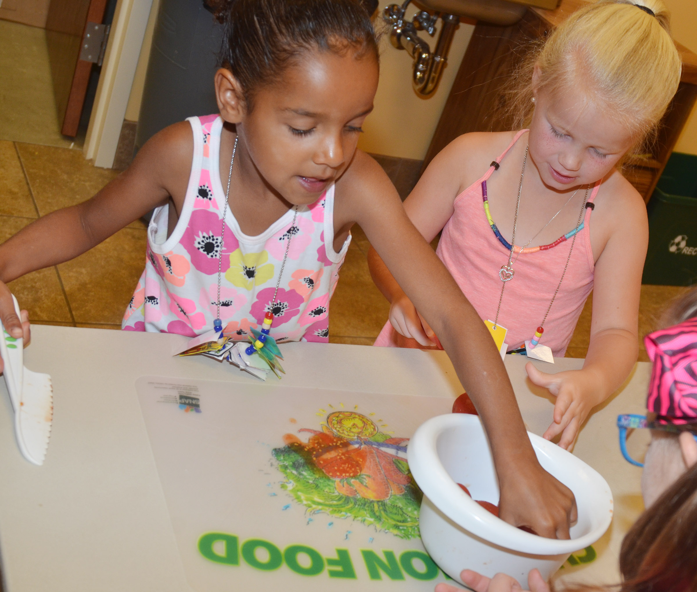 CES kindergarteners Kaylee Thompson, at left, and Lillie Judd cut tomatoes as they make salsa.