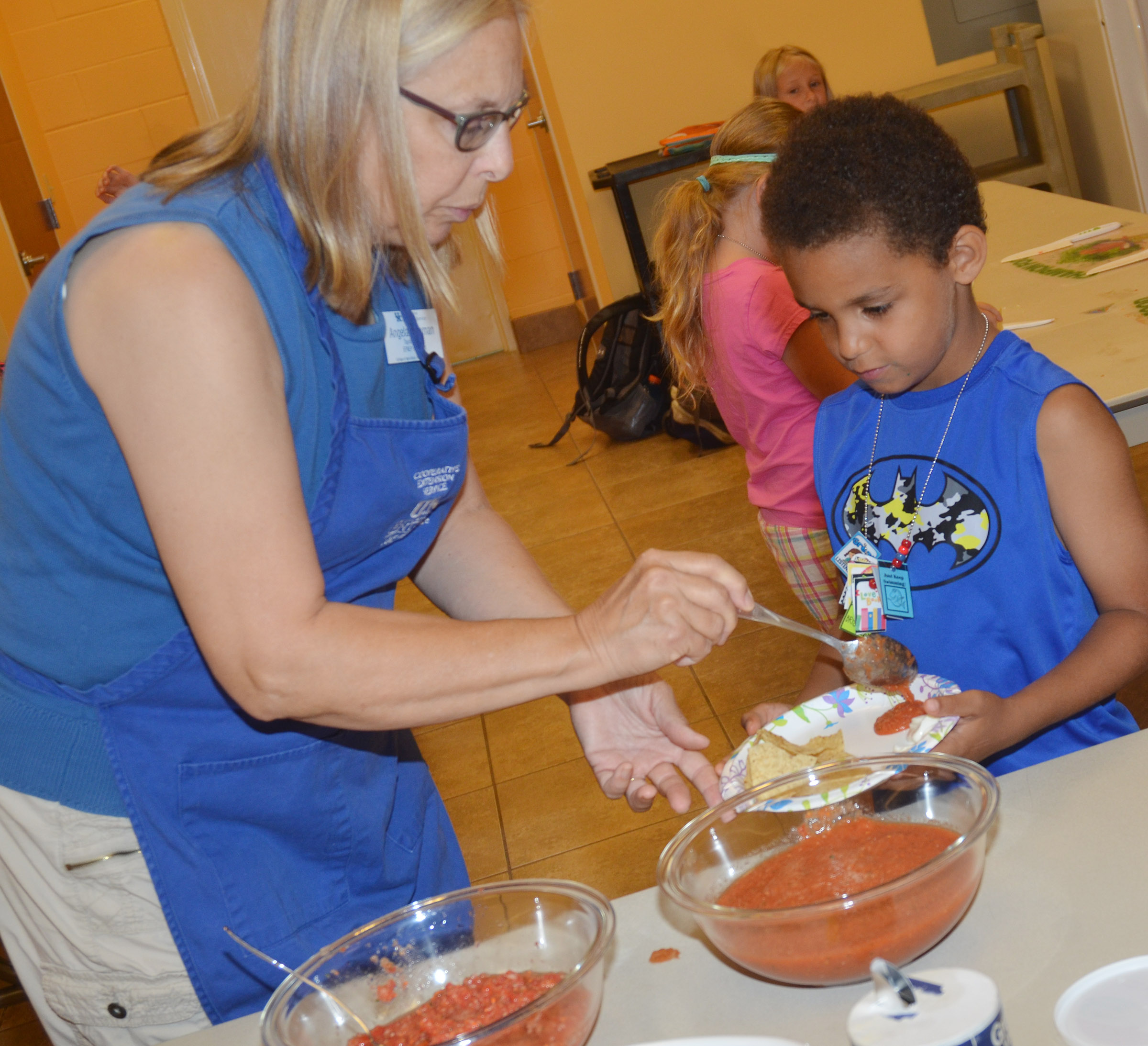 Angie Freeman, expanded foods and nutrition program assistant at Taylor County Extension Office, gives CES kindergartener Quincy Travis a sample of the salsa he helped make.