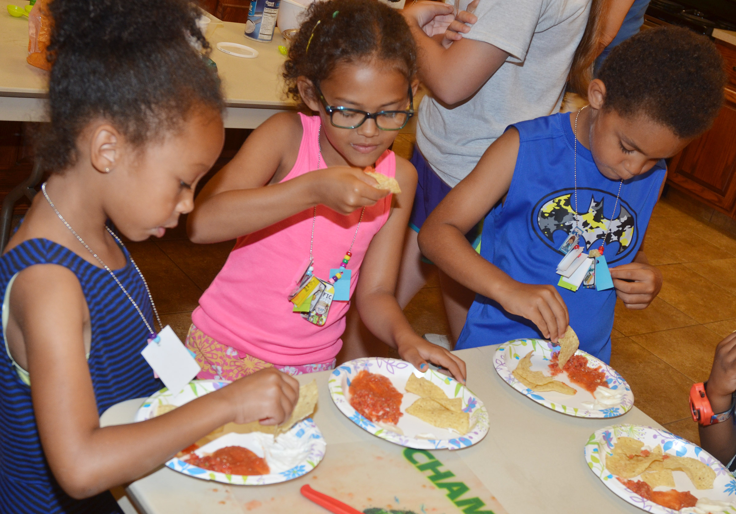 From left, CES kindergarteners Elyzabeth Fisher, Marlee Dickens and Quincy Travis sample the salsa they made.