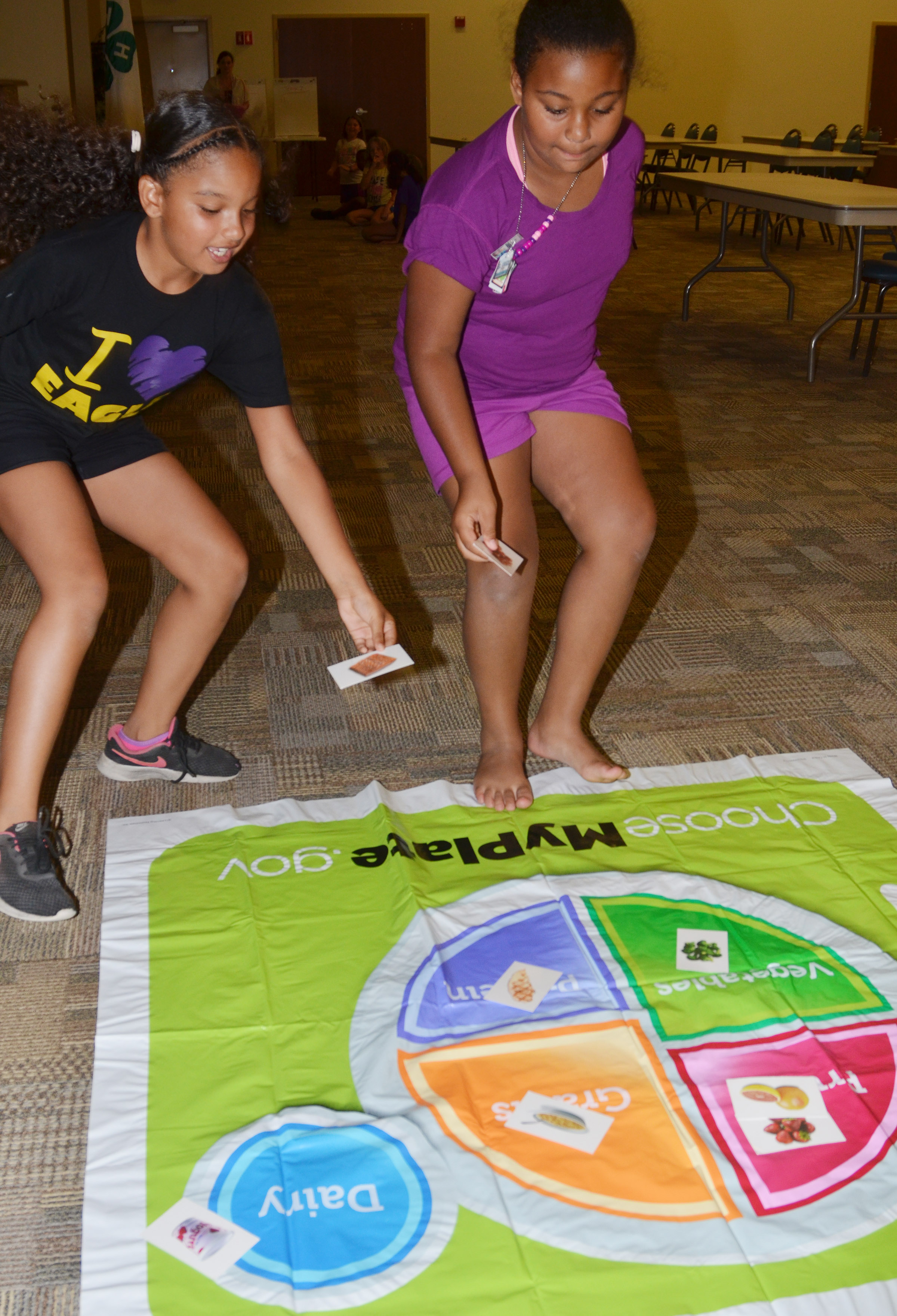 CES third-graders Aleecia Knezevic, at left, and Narissa Barnett race to place their foods in the correct food group.