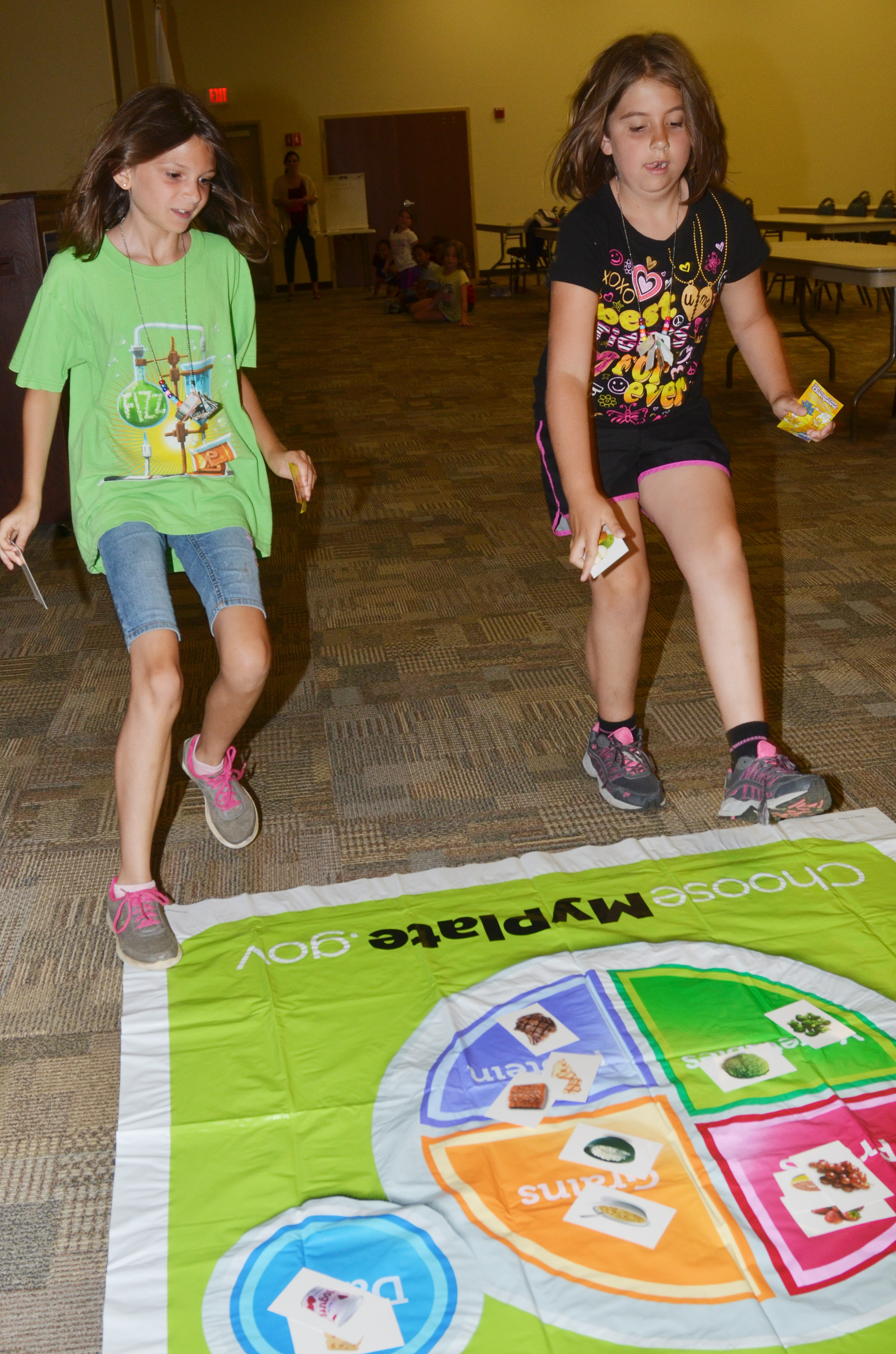 CES third-graders Madie Gebler, at left, and Adrianna Garvin race to place their foods in the correct food group.