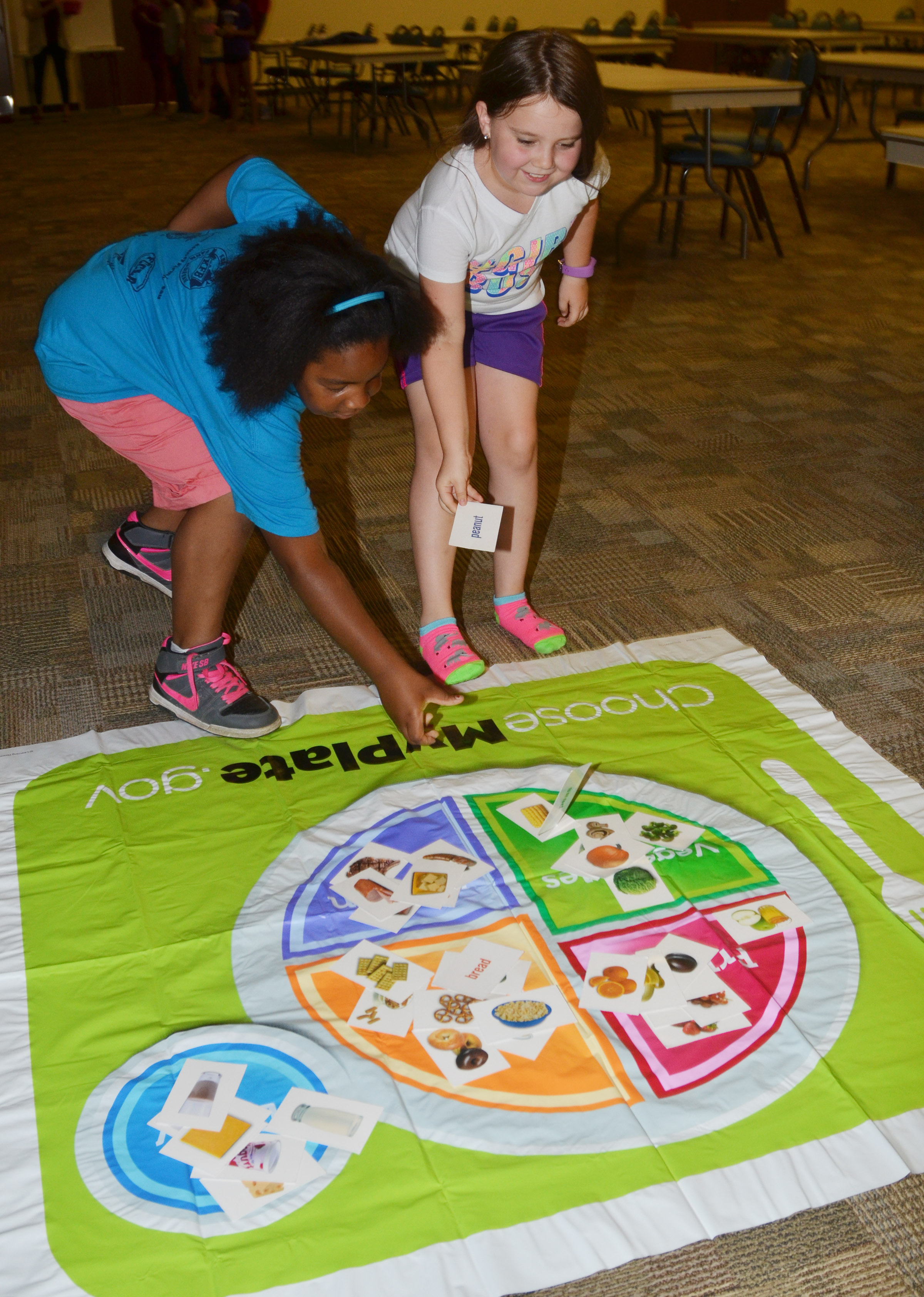 CES third-graders KaMiya Williams, at left, and Maylee Wilds race to place their foods in the correct food groups.