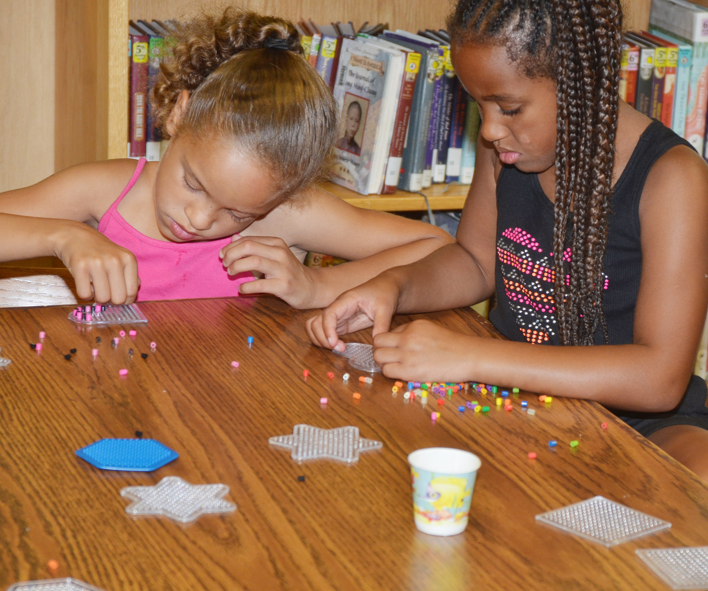CES first-graders Keiava Thompson, at left, and Kadance Ford make bead art.